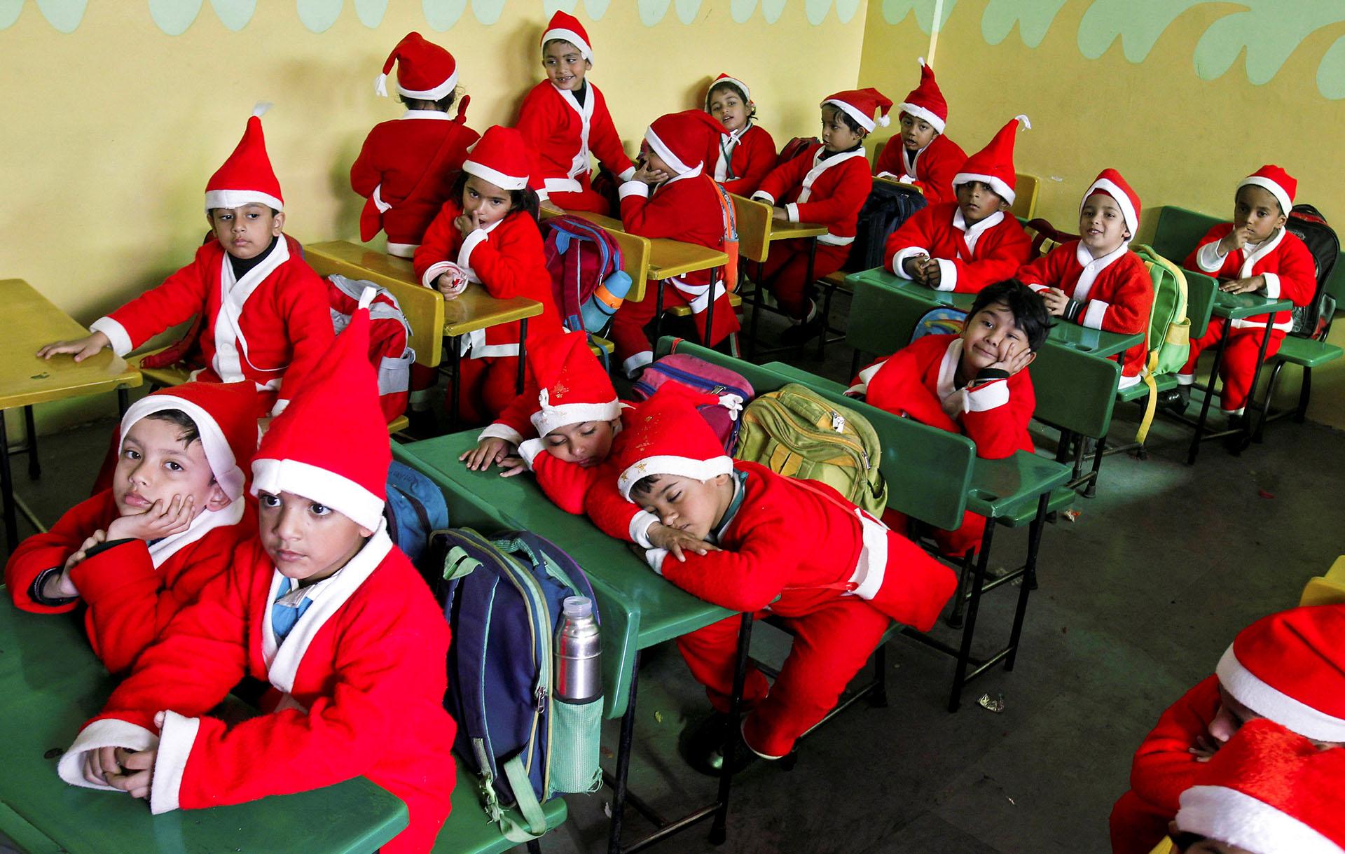 Niños vestidos con trajes de Santa Claus se sientan dentro de un aula antes de participar en las celebraciones navideñas en una escuela de Chandigarh, India, el 20 de diciembre de 2017. (Reuters)