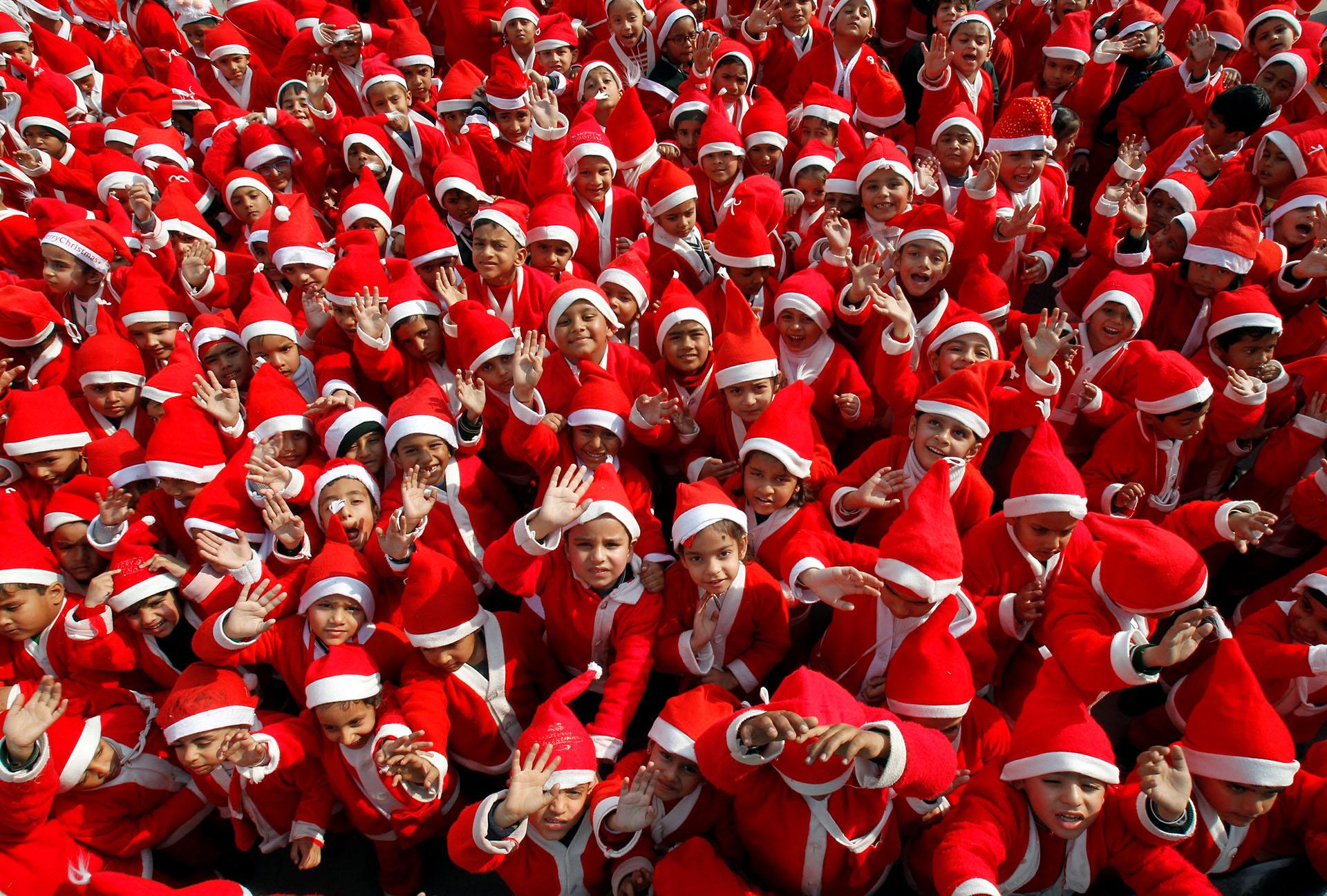 Niños vestidos con trajes de Santa Claus saludan mientras participan en las celebraciones navideñas en una escuela de Chandigarh, India, el 20 de diciembre de 2017. (Reuters)