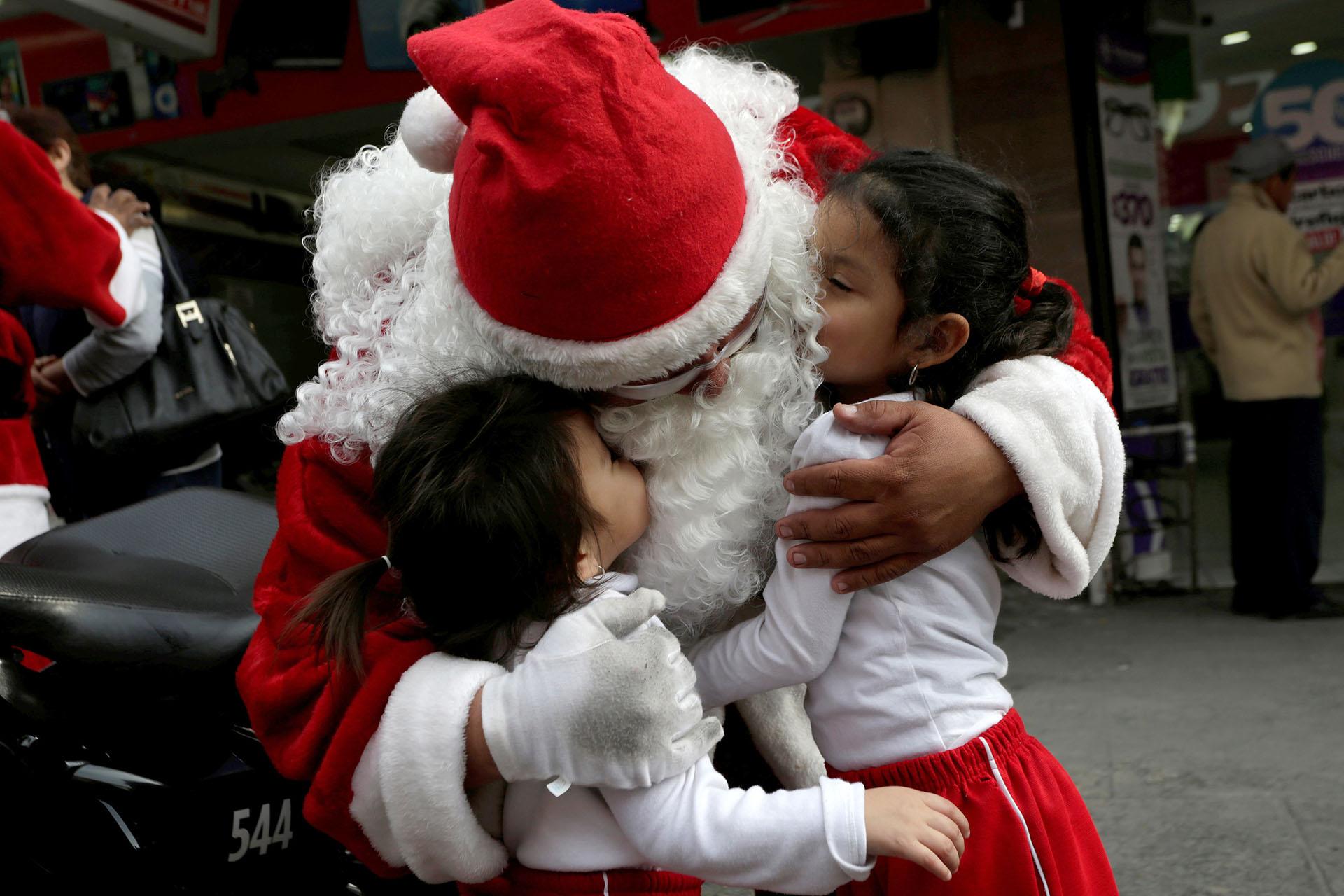 Un miembro de la policía de tránsito vestido como Papá Noel abraza a dos niñas en el centro de Monterrey, México 19 de diciembre de 2017. (Reuters)