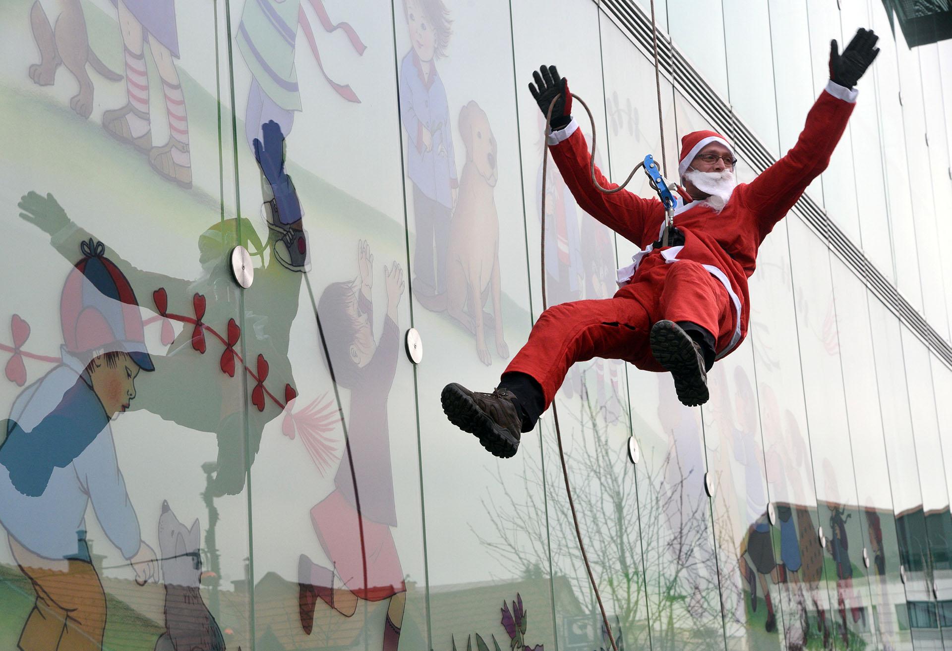 Un miembro del Servicio de Rescate de Montaña vestido con un traje de Papá Noel se acerca a los pacientes mientras desciende del techo de una clínica pediátrica en Ljubljana, Eslovenia, el 19 de diciembre de 2017. (Reuters)