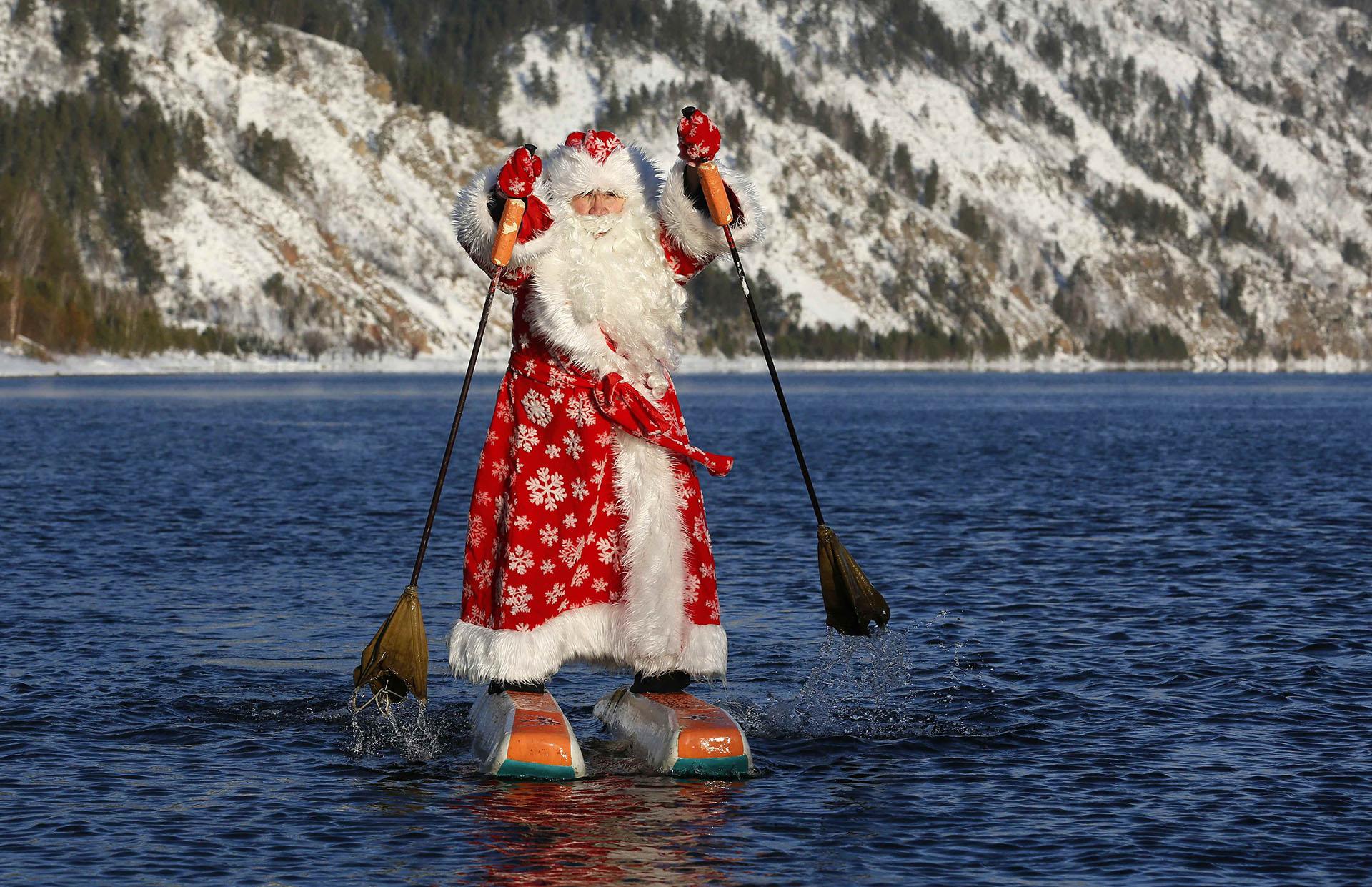 Nikolai Vasilyev, de 64 años, vestido como el padre Frost, el equivalente ruso de Santa Claus, hace esquí acuático a lo largo del río Yenisei, en las afueras de la ciudad siberiana de Krasnoyarsk, Rusia, el 19 de diciembre de 2017. (Reuters)