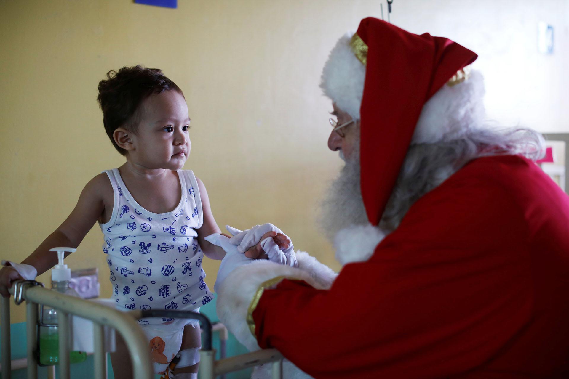 El islandés Einar Sveinsson, vestido de Papá Noel, habla con Javier Steven Cabrera Henríquez durante una visita al Benjamin Bloom National Children Hospital en San Salvador, El Salvador, el 18 de diciembre de 2017. (Reuters)
