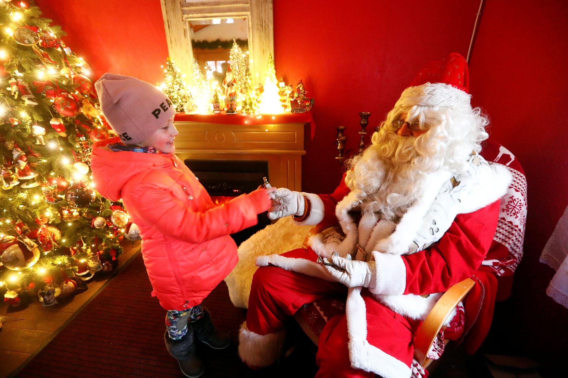 Un hombre vestido de Papá Noel da dulces a una niña en Tallinn, Estonia 18 de diciembre de 2017. (Reuters)