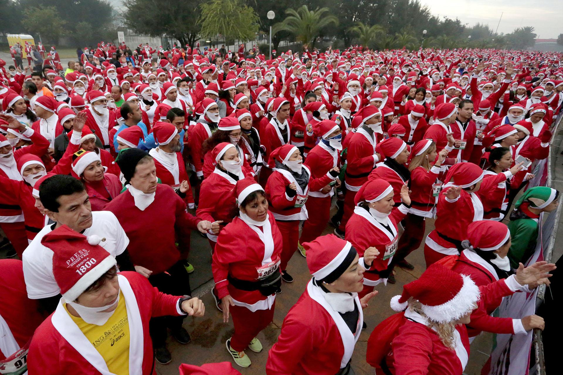 """Corredores participan en la carrera anual conocida como """"Run Santa Run"""" en el Parque Fundidora en Monterrey, México el 17 de diciembre de 2017. (Reuters)"""