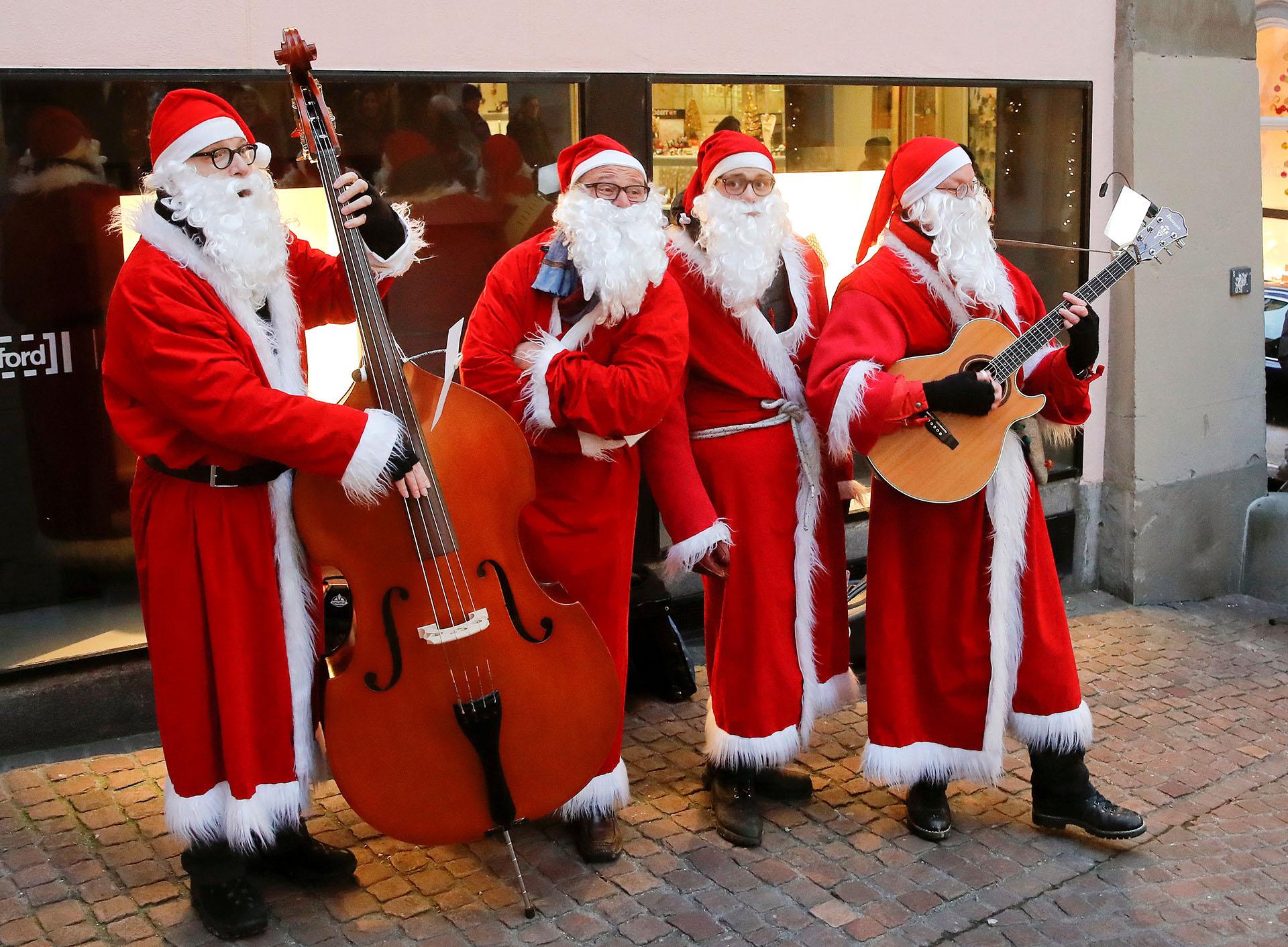 Los miembros del cuarteto vocal de jazz navideño Singing Santas actúan en la ciudad vieja de Zúrich, Suiza, el 17 de diciembre de 2017. (Reuters)