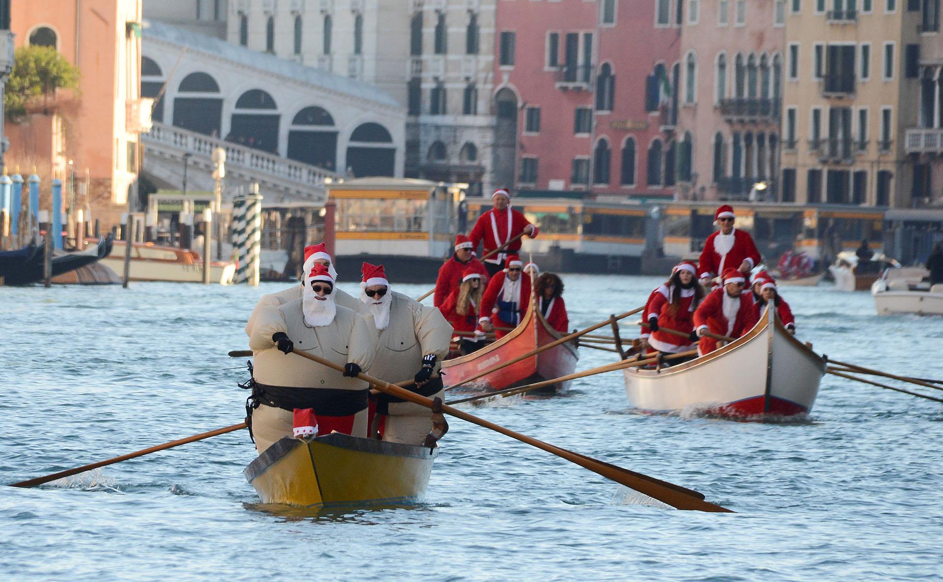 Gente vestida como Santa Claus rema durante una regata navideña en Venecia, Italia 17 de diciembre de 2017. (Reuters)