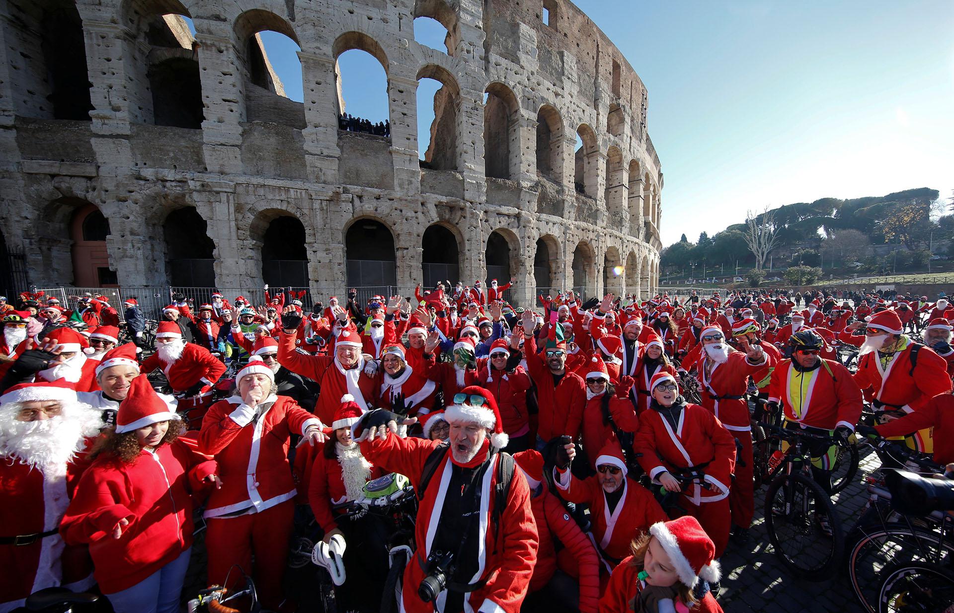 Más de cien ciclistas vestidos de Papá Noel se reúnen en el Coliseo de Roma, Italia, el 17 de diciembre de 2017. (Reuters)