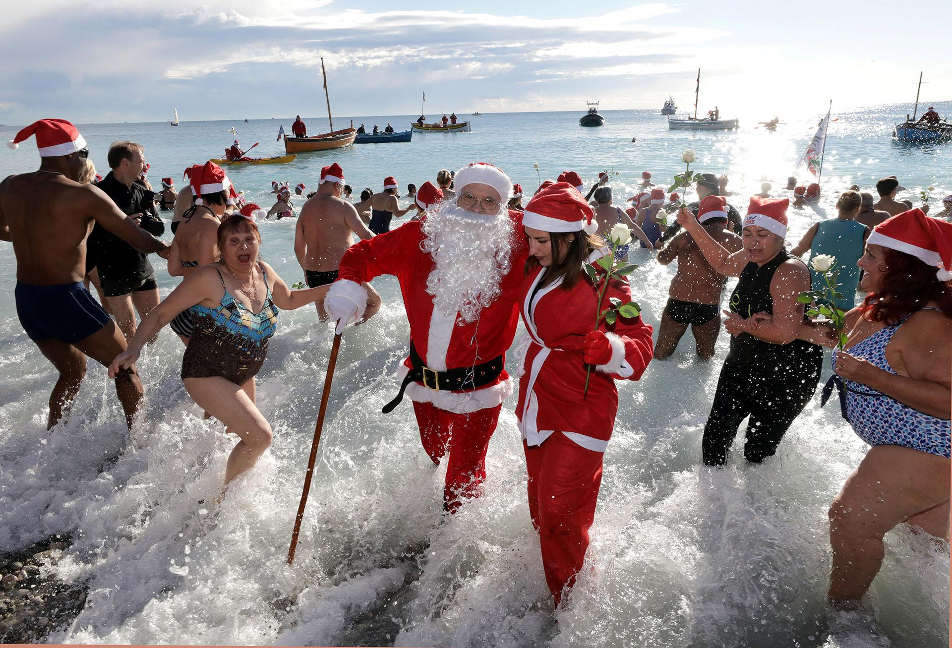 Un hombre vestido de Papá Noel participa en el tradicional baño navideño en Niza, Francia, el 17 de diciembre de 2017. (Reuters)