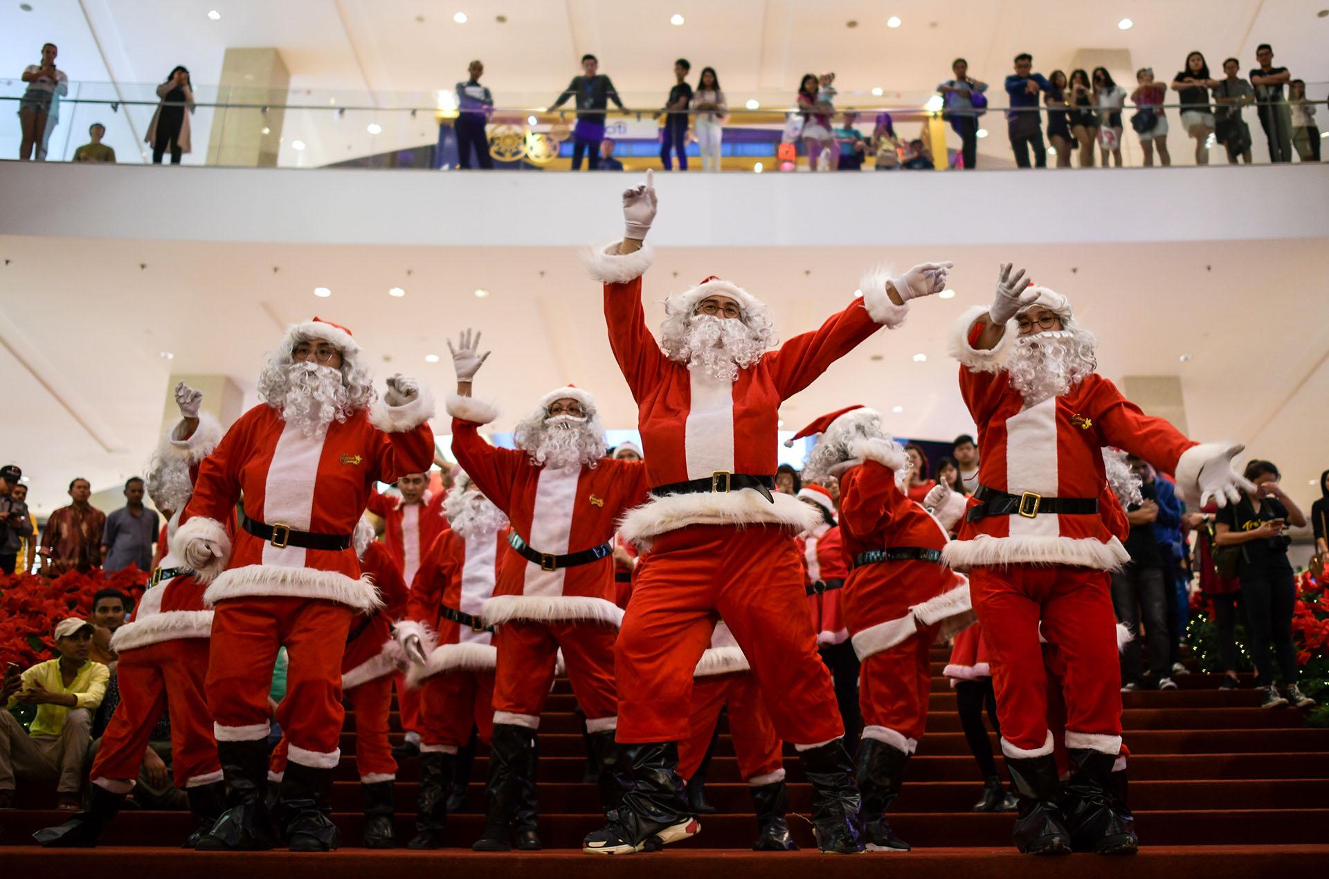 Intérpretes vestidos con trajes de Santa Claus bailan en un centro comercial en Kuala Lumpur el 18 de diciembre de 2017. (AFP)