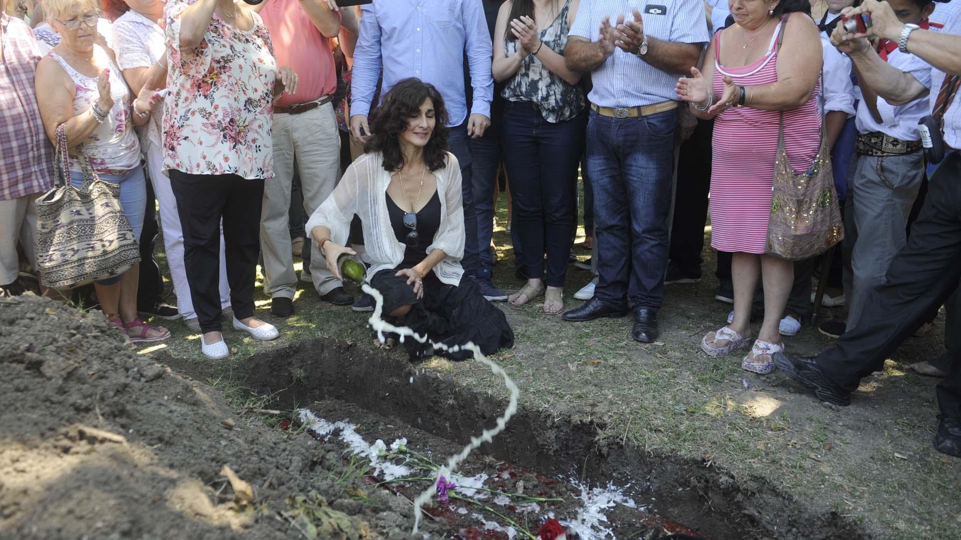 Entre lágrimas, Micaela Cruz arroja champán sobre el cajón de su papá, Lito Cruz. Los restos del actor, uno de los más prestigiosos de la escena nacional,fueron enterrados el viernes 22 de diciembre en el Cementerio Municipal de Berisso. Además del champán, hubo guitarreadas y jinetes. Y una honda tristeza (Dino Calvo)