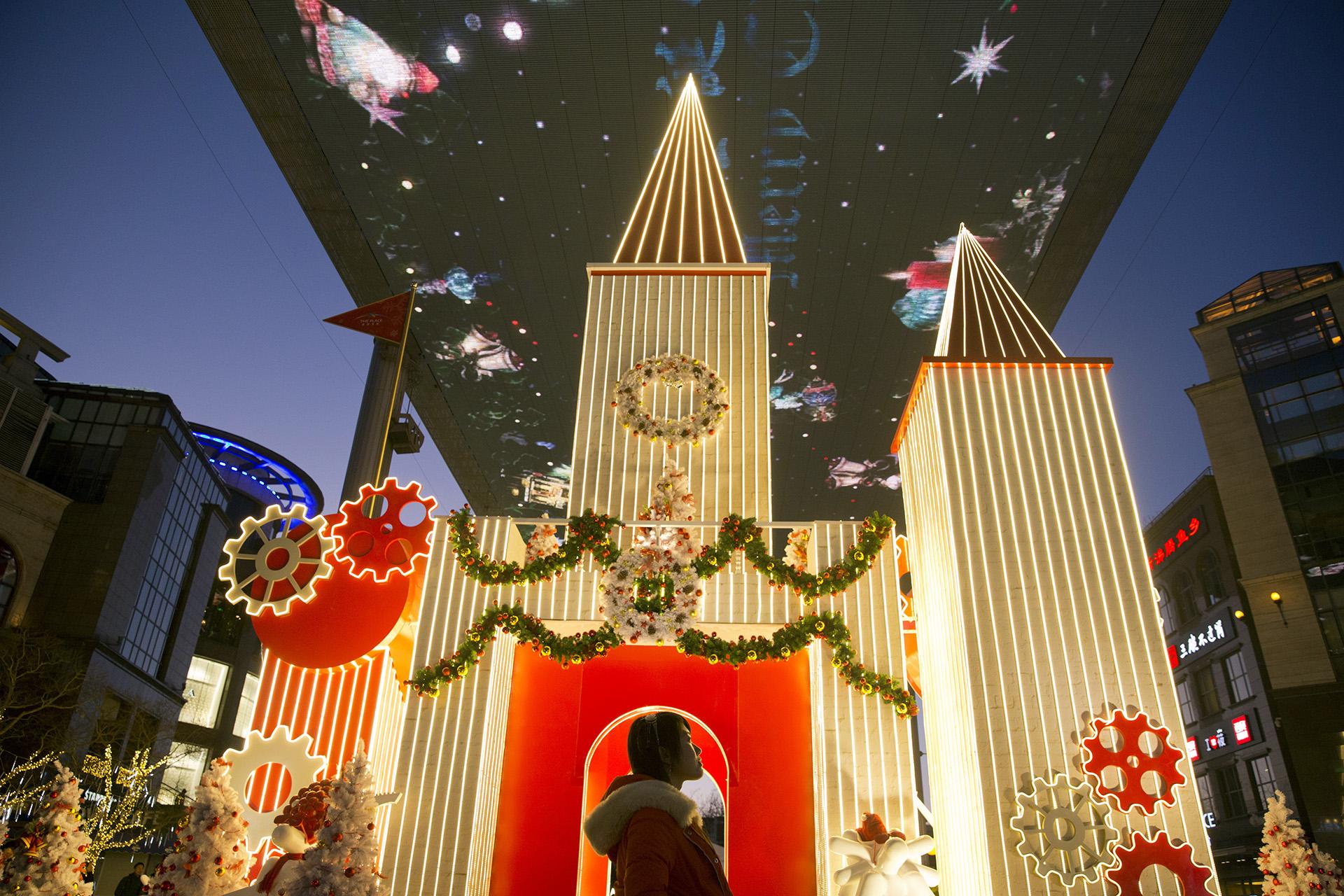 Una mujer china participa de los festejos por la llegada de la Navidad ante un adorno navideño dispuesto en un centro comercialenBeijing