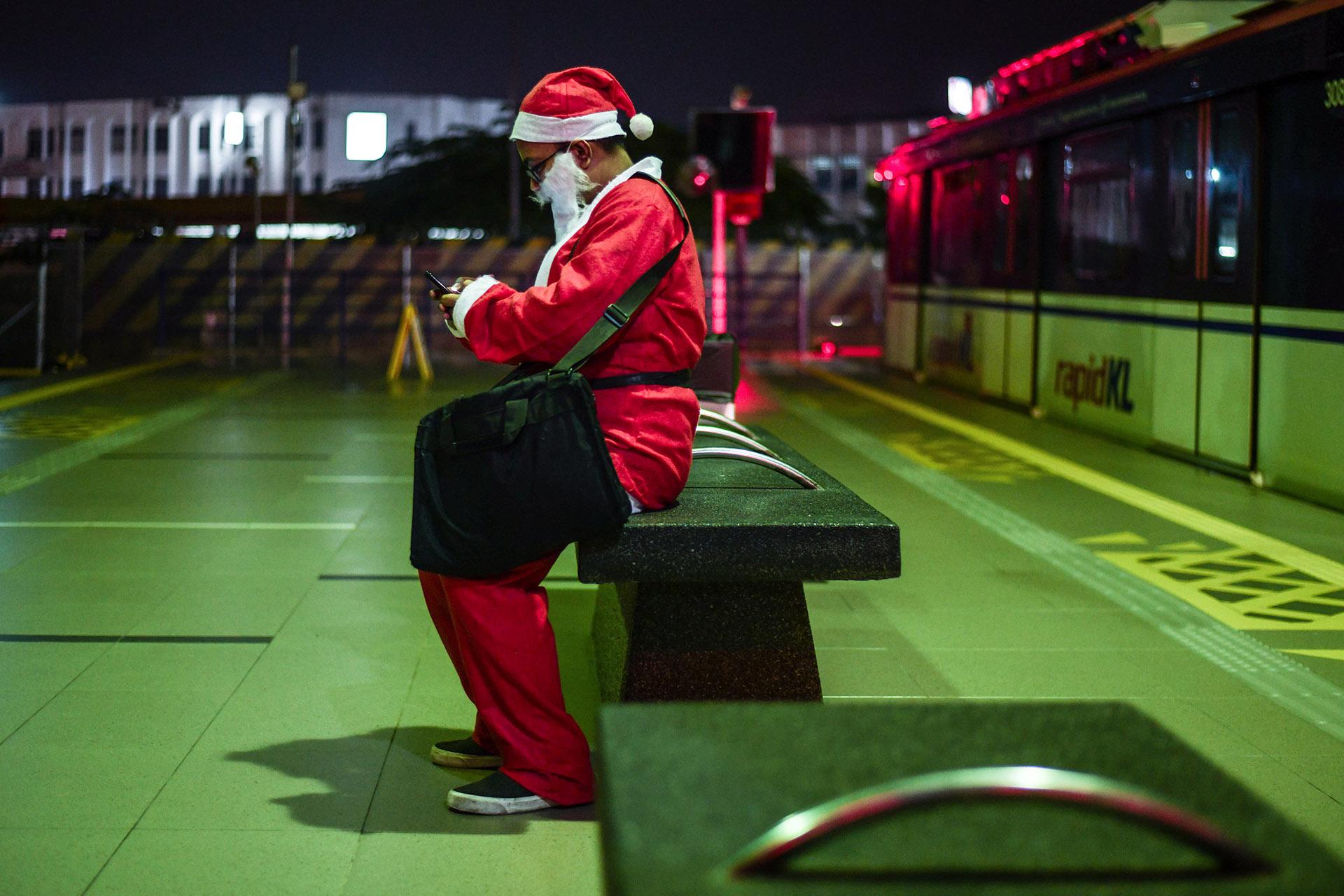 Un hombre disfrazado de Papa Noel espera en una estación de tren en Kuala Lumpur