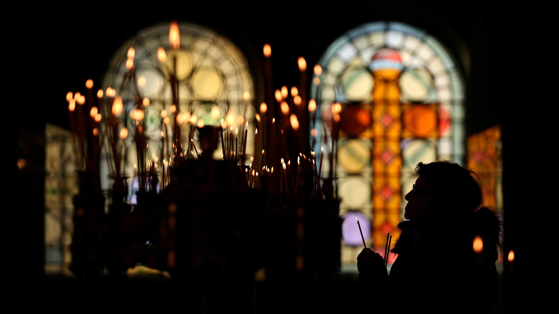 Una mujer sostiene una vela mientras asiste a una misa en Navidad en la catedral de San Alejandro Nevski en Sofía, Bulgaria