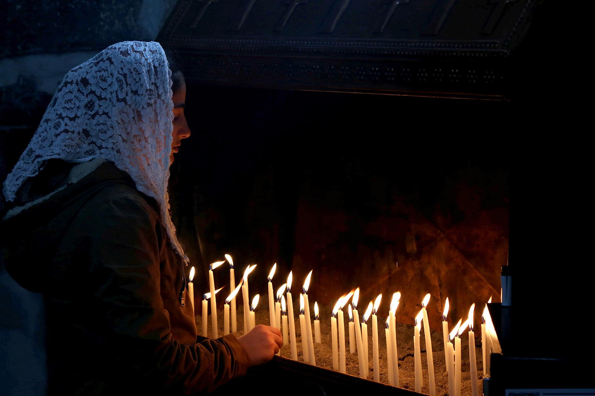 Una mujer cristiana enciende velas en una misa en Siria