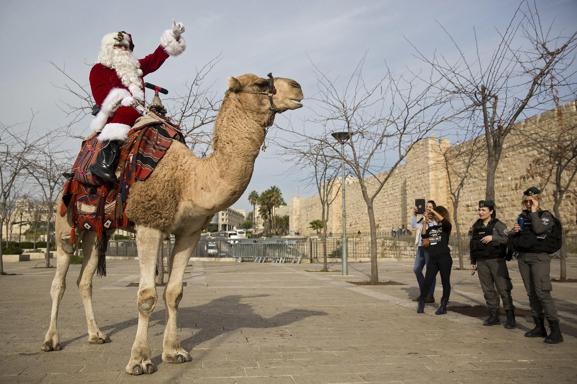 Un hombre vestido de Santa Claus monta un camello en la puerta de Jaffa en la Ciudad Vieja de JerusalAi??n