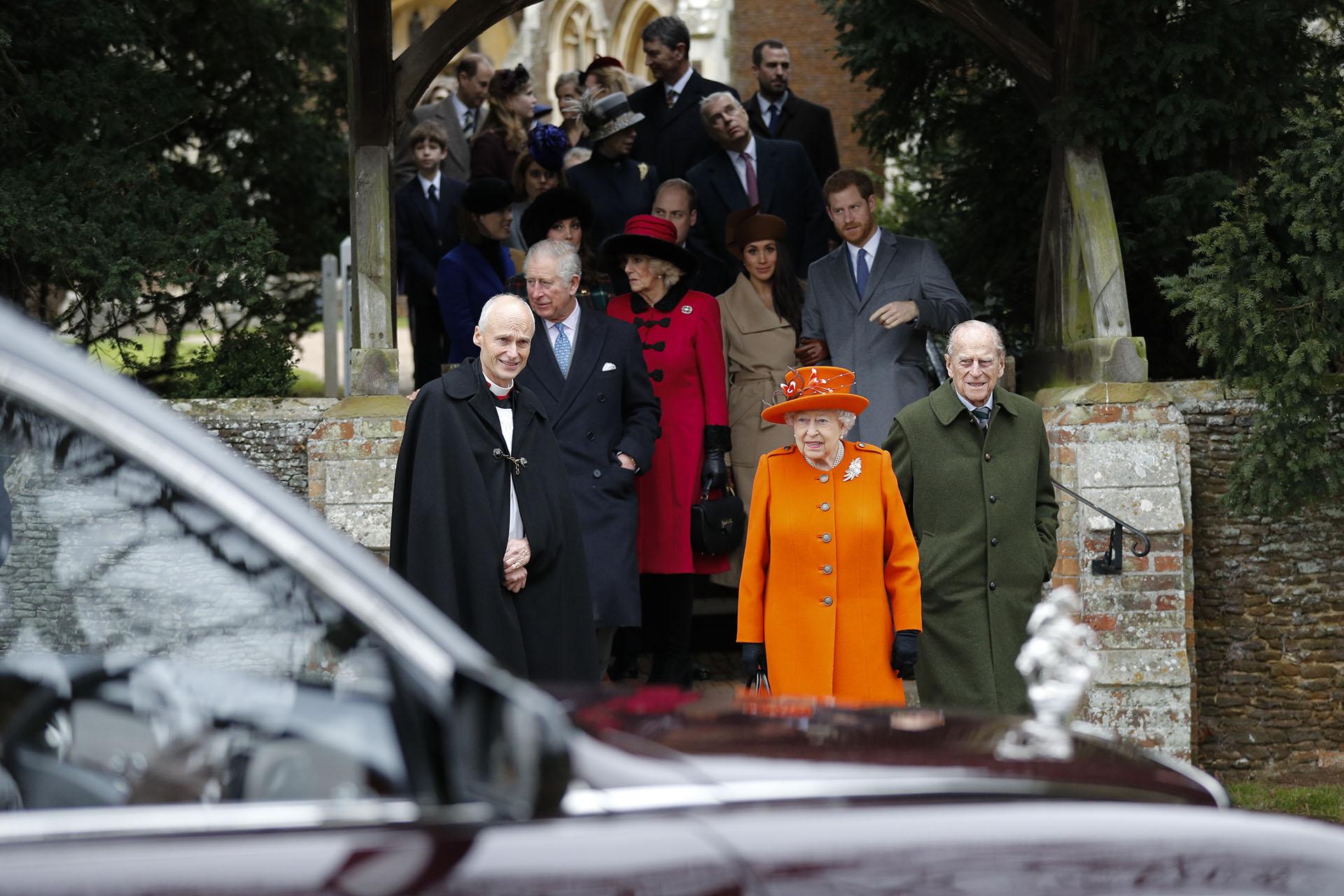 Vestida con su habitual estilo monocromático, esta vez de colorado, la monarca camina junto a su marido Felipe, duque de Edimburgo, y al Reverendo Jonathan Riviere