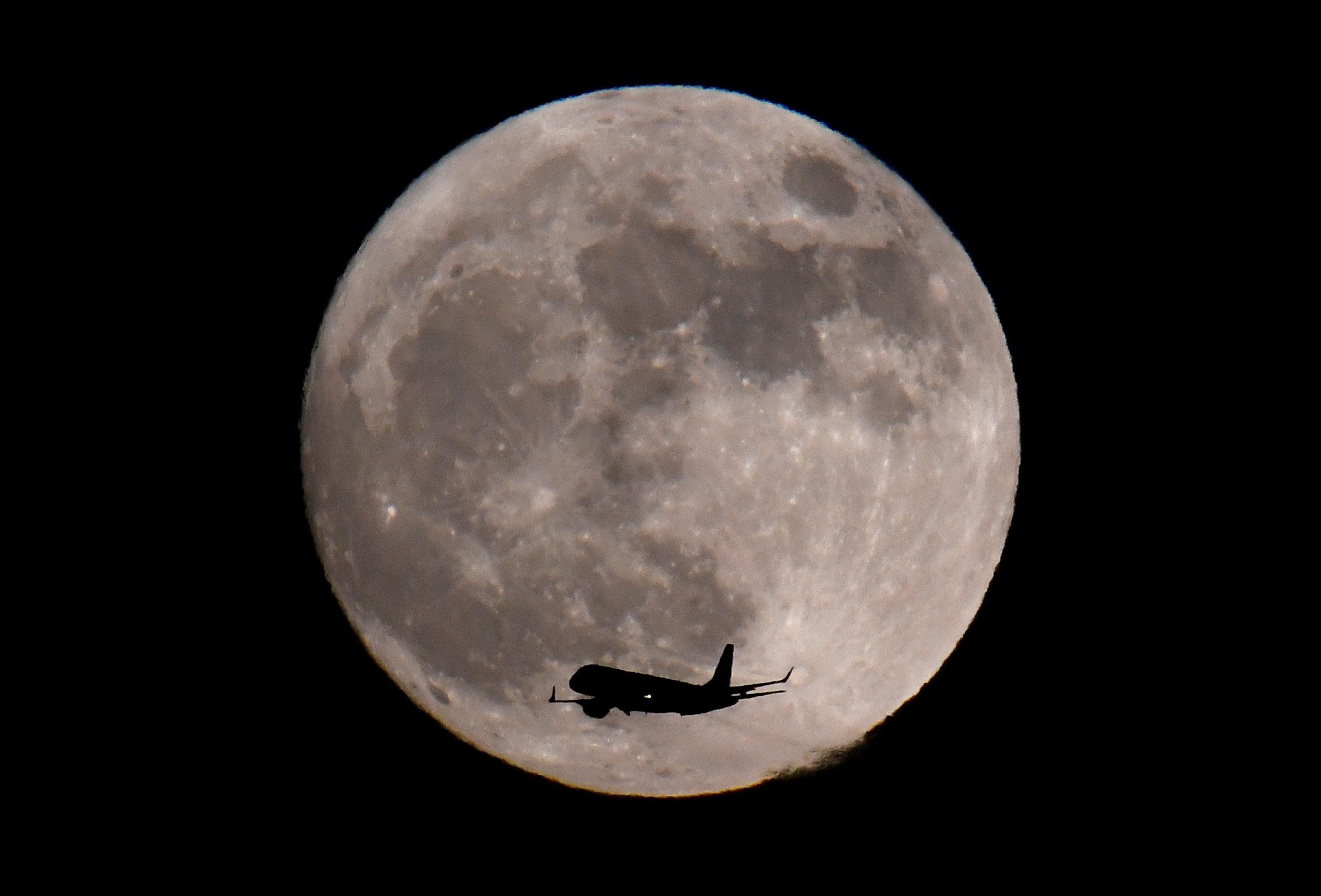 Un avión aterriza bajo la luz de la superluna en el aeropuerto deHeathrow en Londres, Reino Unido (REUTERS/Toby Melville)