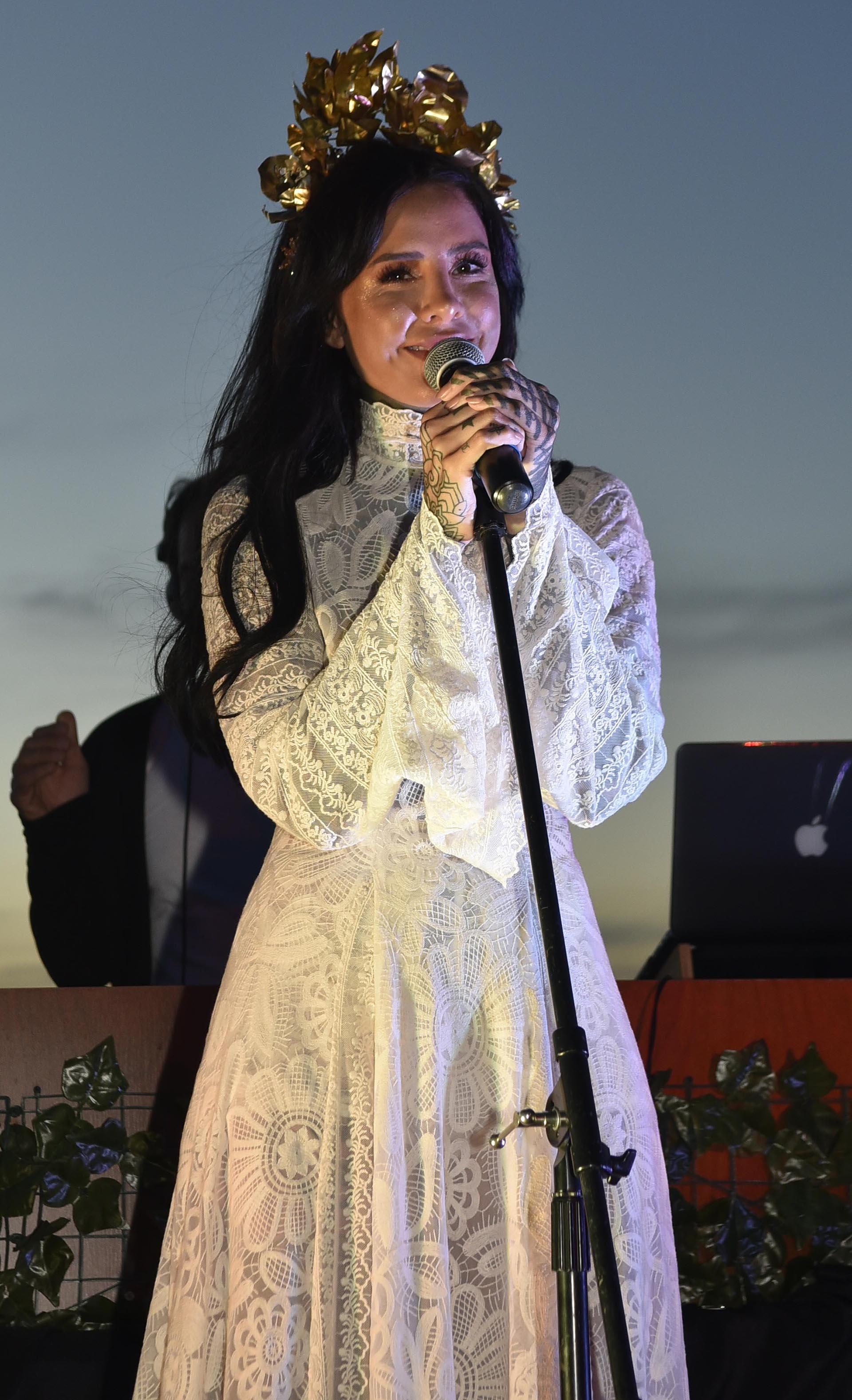 Cande Tinelli en su presentación con vestido largo realizado en encaje con mangas largas y cuello cisne. La corona fue el detalle que coronó su look.