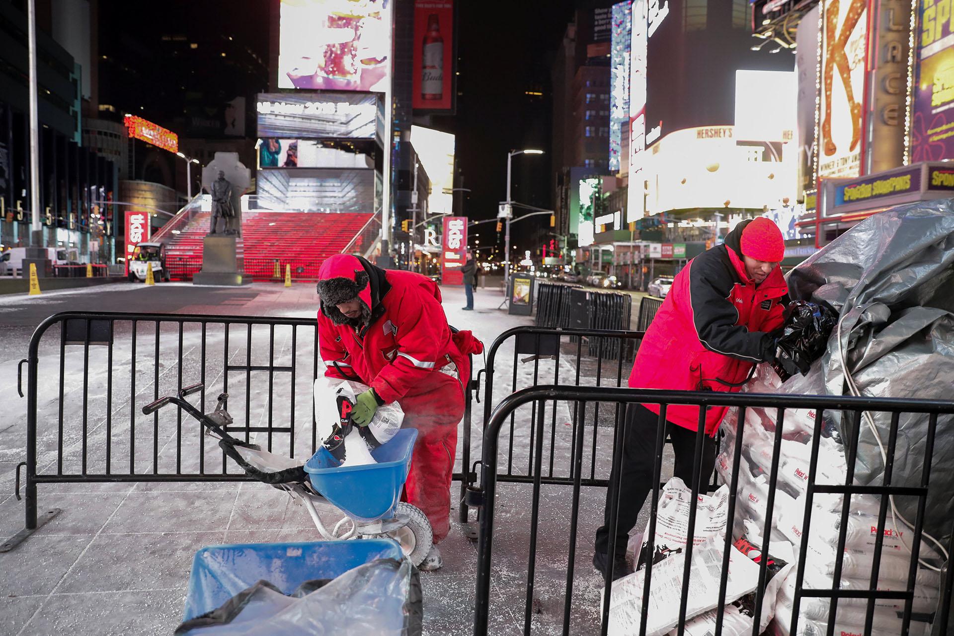 Trabajadores arrojan sal para derretir el hielo en pleno Times Square, en Manhattan(REUTERS/Jeenah Moon)