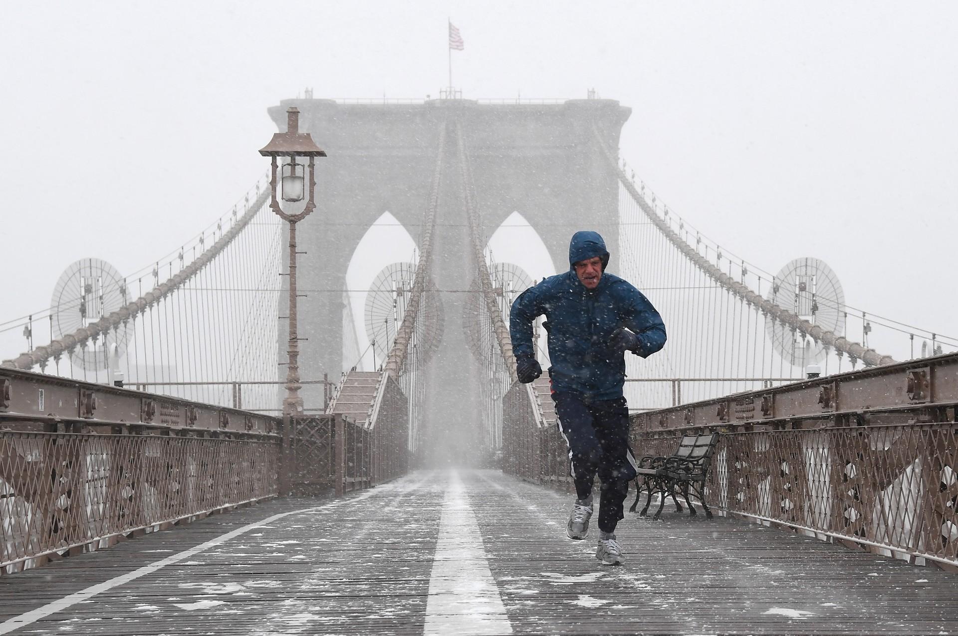 Un corredor pasa por el puente Brooklyn en medio de la nevada
