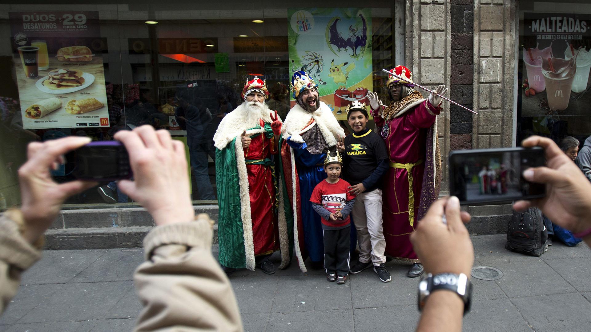 Los niños posan con artistas callejeros vestidos como los tres Reyes Magos, como parte de las celebraciones del Día de los Reyes Magos, en el centro histórico de la Ciudad de México (AP)