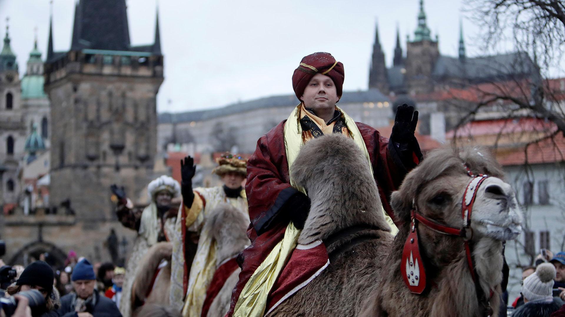 Hombres vestidos como los Reyes Magos saludan a los espectadores mientras montan camellos durante la procesión de los Reyes Magos al otro lado del puente medieval de Carlos, como parte de una recreación de la escena de la Natividad, en Praga, República Checa (Reuters)