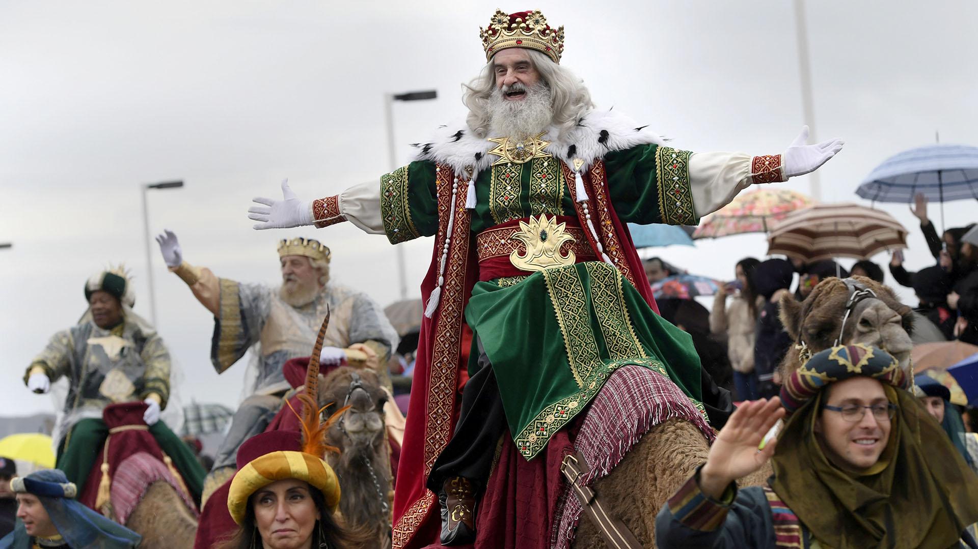 Un hombre vestido como uno de los Reyes Magos saluda a la gente durante el desfile de la Epifanía en Gijón, España (Reuters)