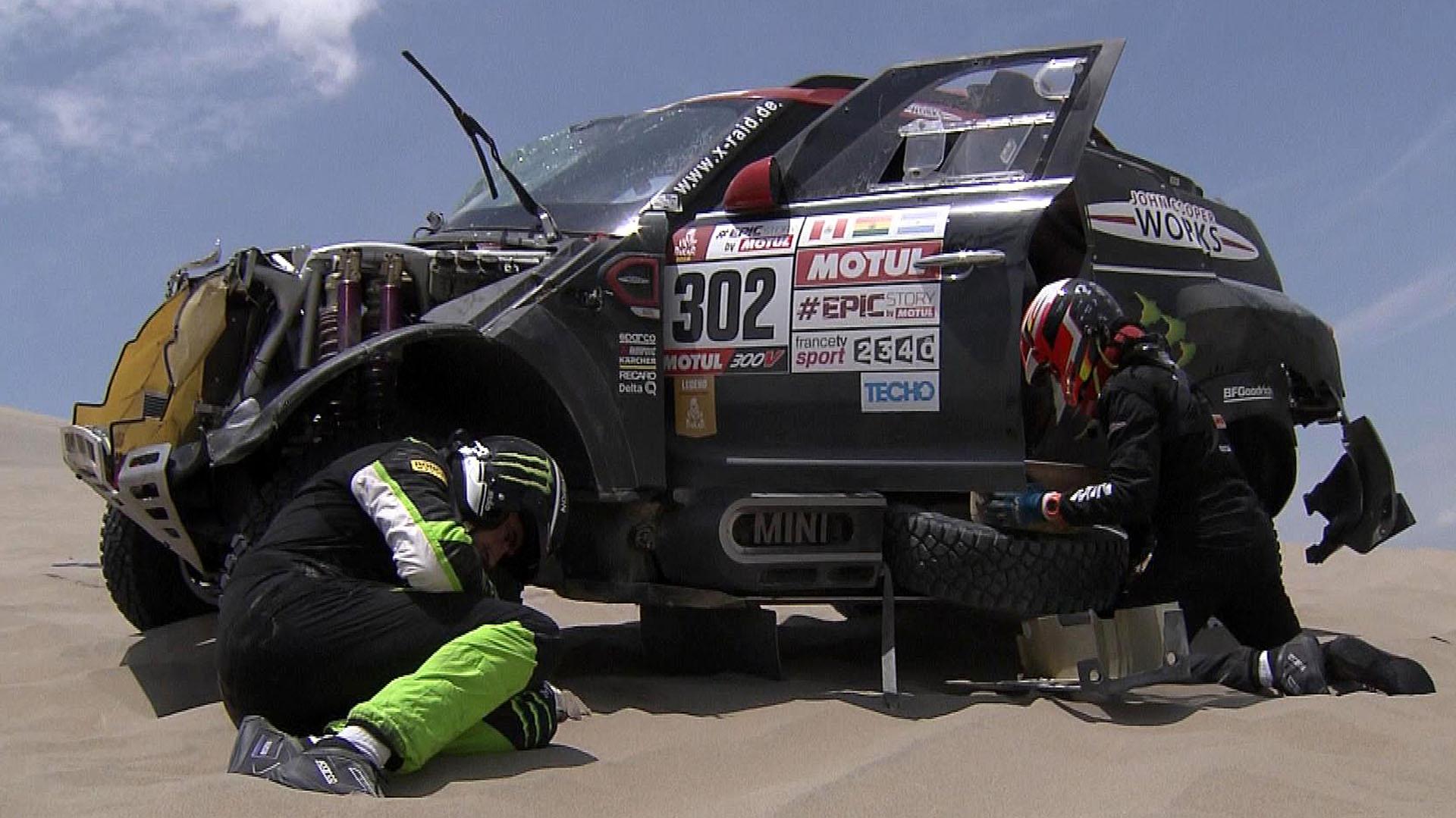 Nani Romaestá dolido y su copiloto, Alex Haro, pone el coche en condiciones para finalizar la etapa (AFP)