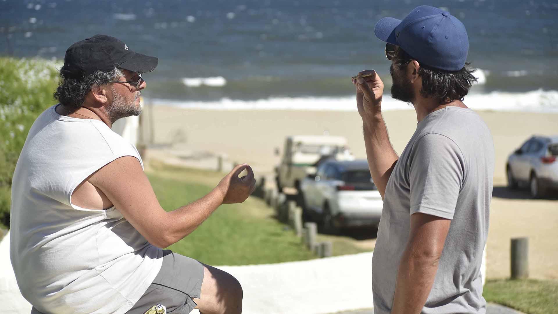Con la playa de fondo, dos hombres compartiendo un cigarrillo de marihuana GM Press Punta
