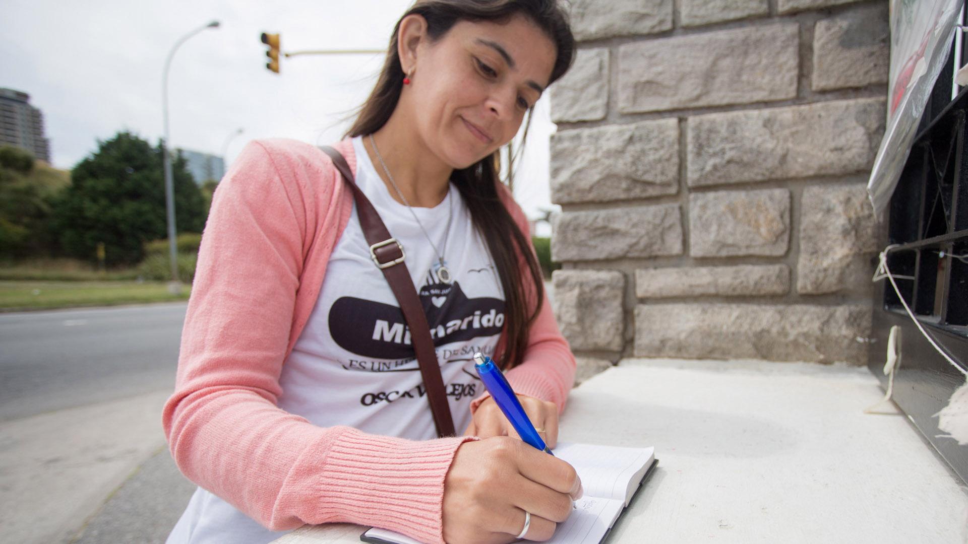 Paola escribe en la puerta de la Base Naval de Mar del Plata (Christian Heit)