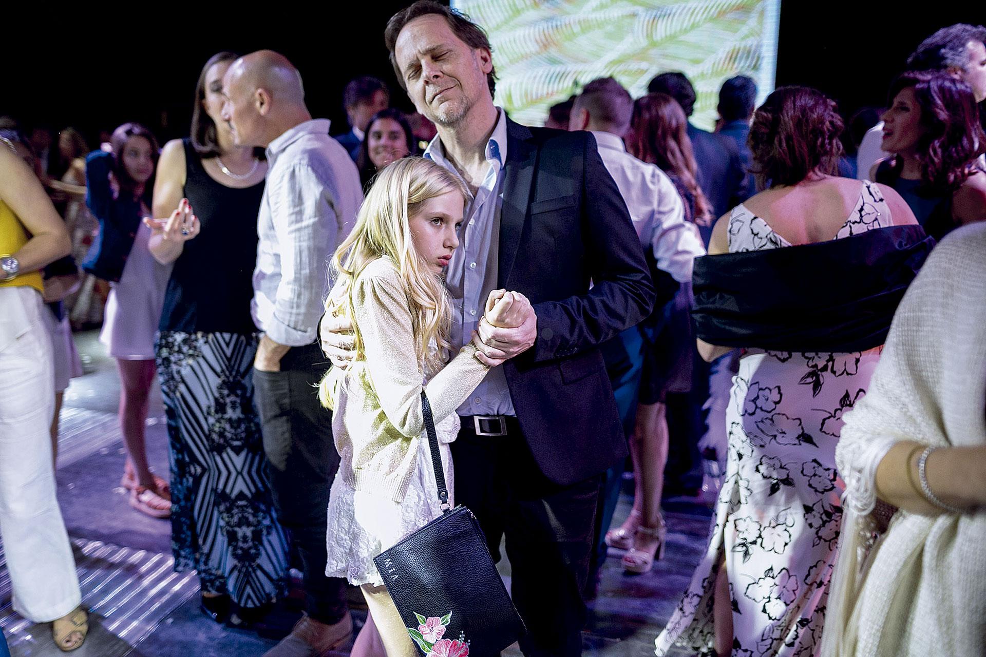 Papá baila un lento con su hija en el casamiento de su amigo. El detalle de la cartera de Mía customizada con su nombre.