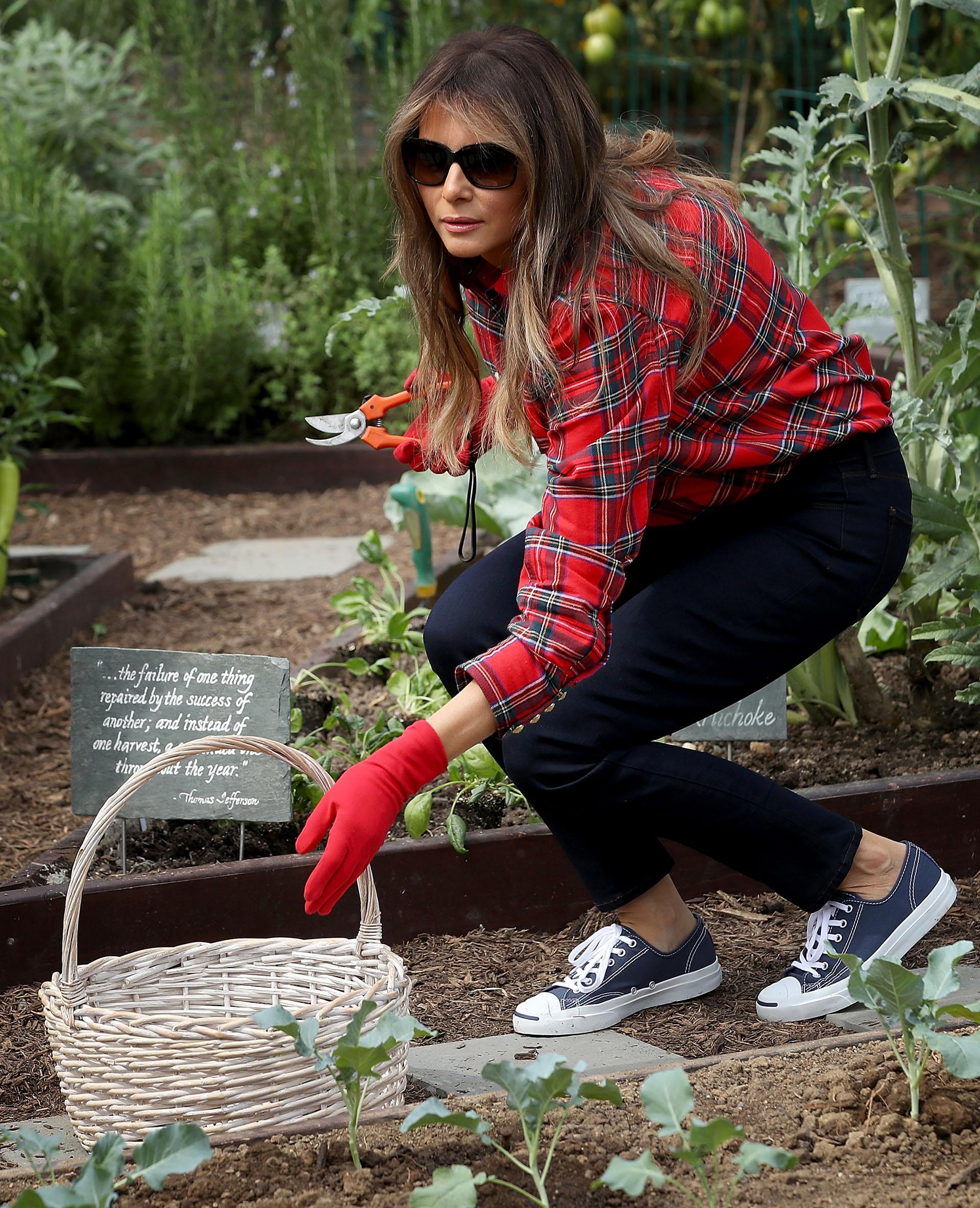 Melania tambiéntiene un costado informal: con camisa escocesa, pantalones negros y zapatillas. El detalle: los guantes combinados con la camisa y los anteojos de sol