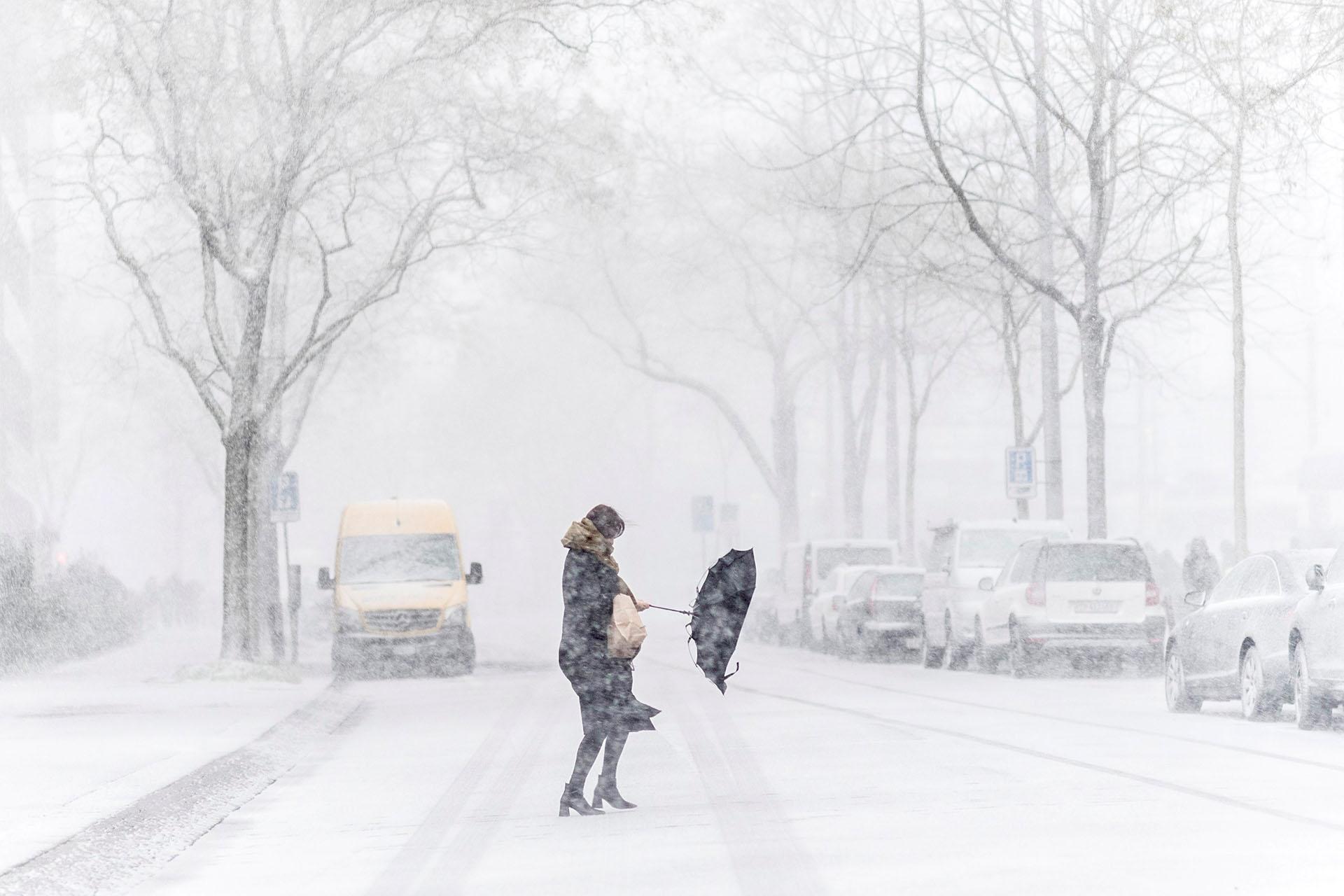 Una mujer se pelea con su paraguas durante una tormenta de nieve en una calle de Zúrich (Suiza) el 17 de enero de 2018 (EFE)