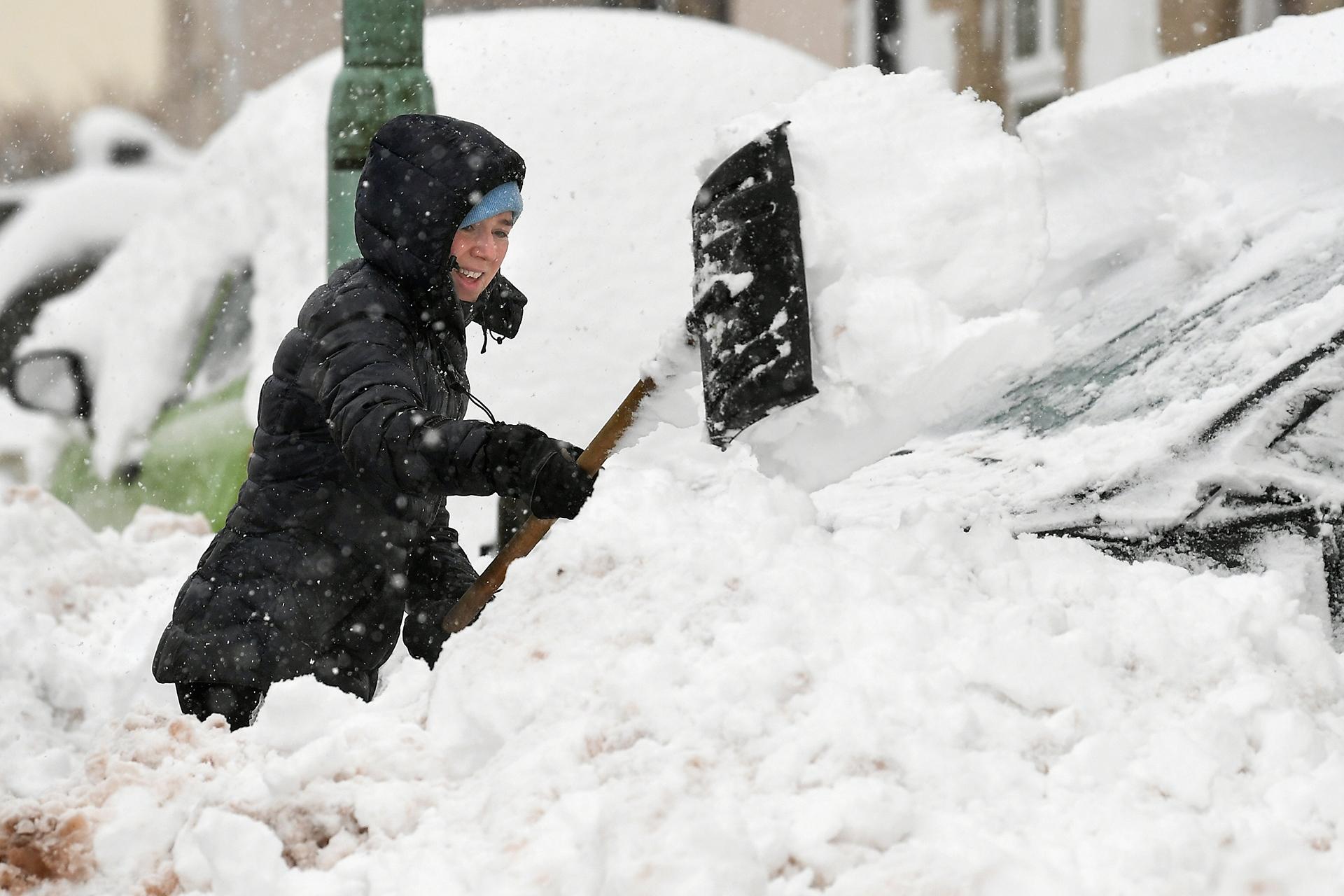 Una mujer quita la nieve de su puerta principal el 17 de enero de 2018 en Leadhills, Escocia (Getty)