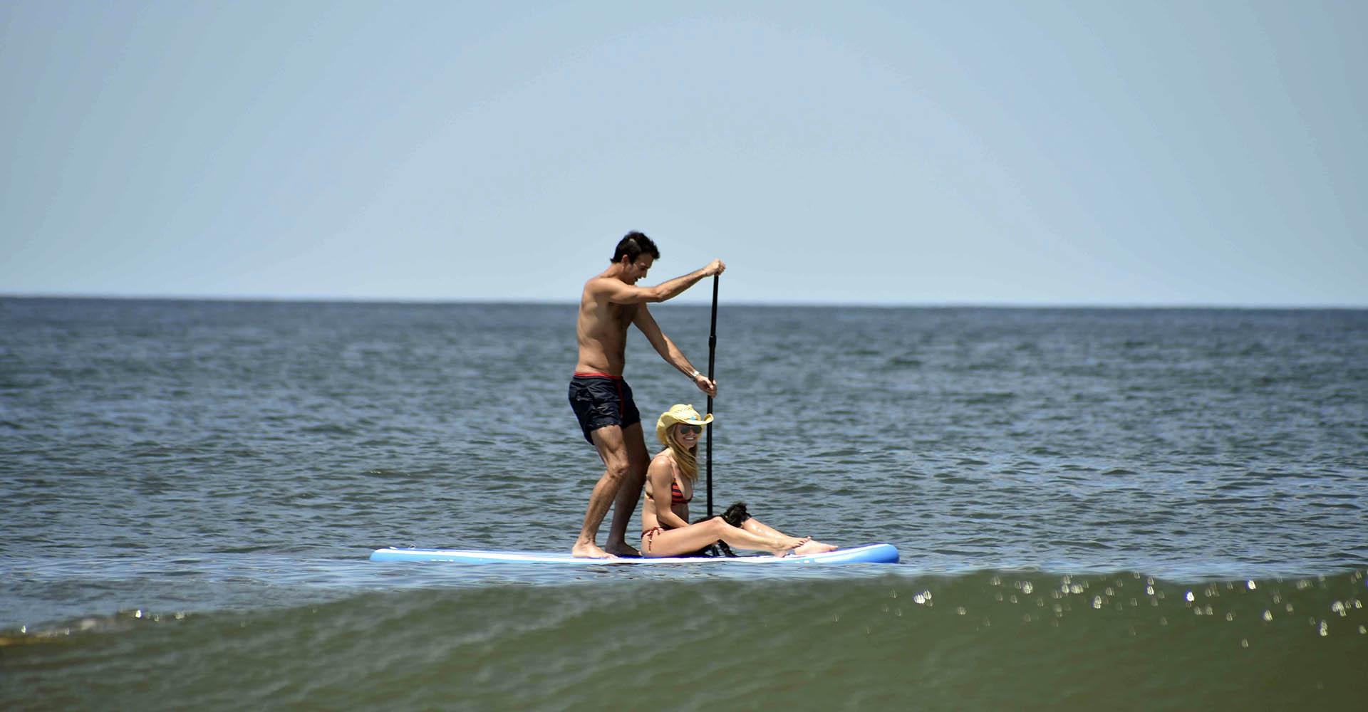 Sofia, con su pareja y su mascota disfrutaron del mar subidos a una tabla de surf