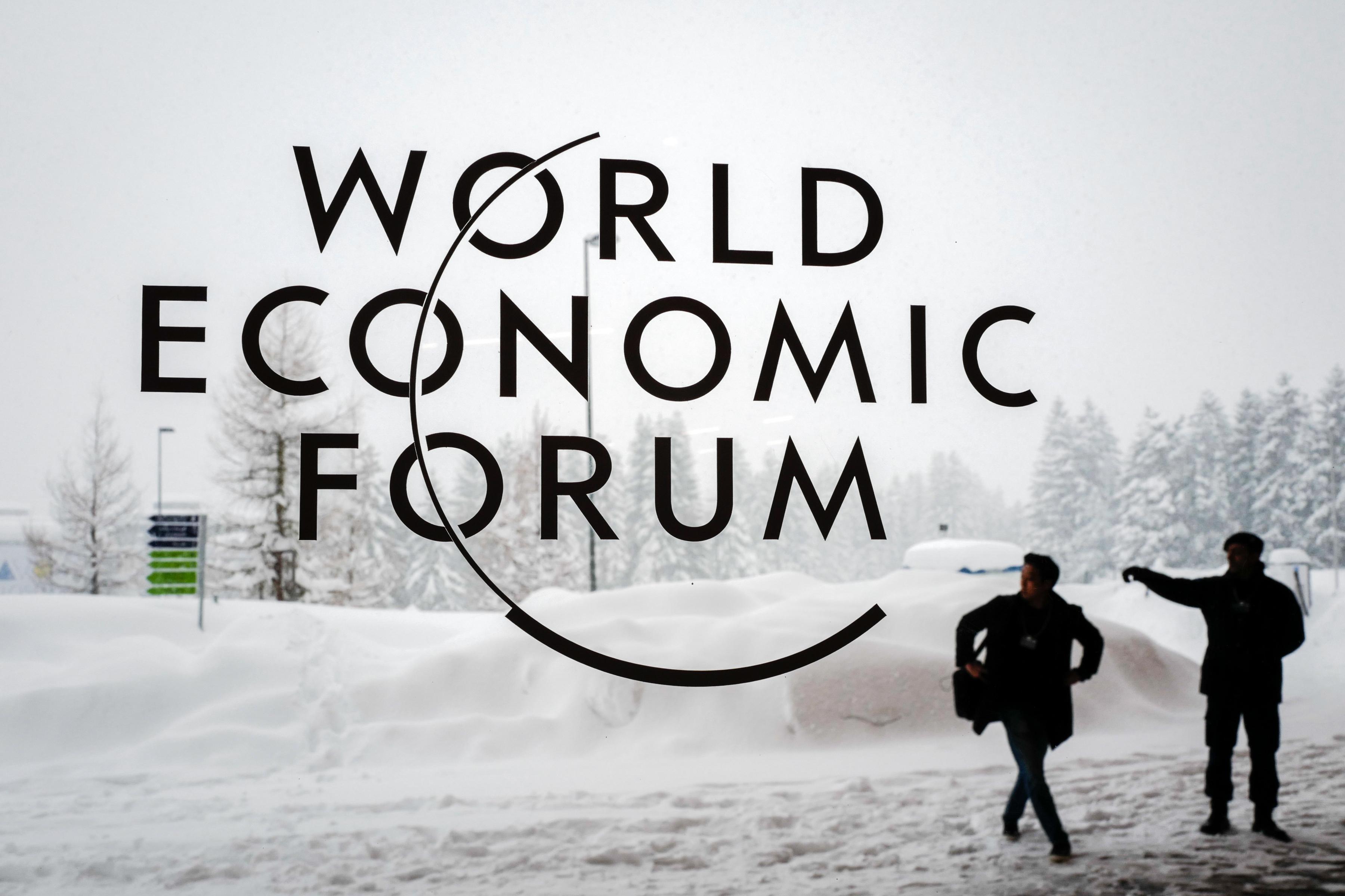 Un guardia de seguridad muestra la dirección a un asistente del foro económico de Davos (AFP PHOTO / Fabrice COFFRINI)