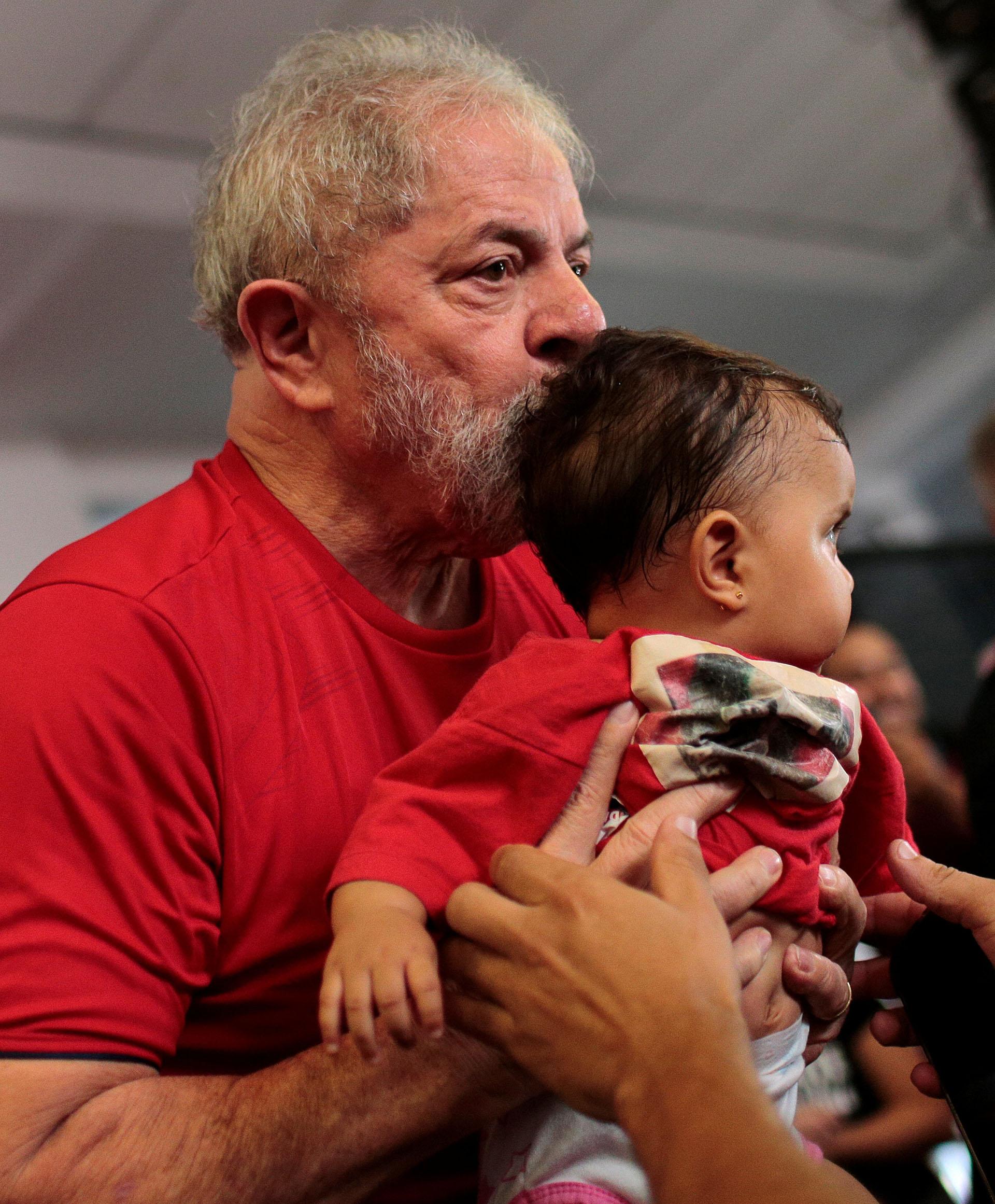 El ex presidente besa a un niño a su llegada al sindicato metalúrgico, lugar desde donde sigue el juicio (Reuters)