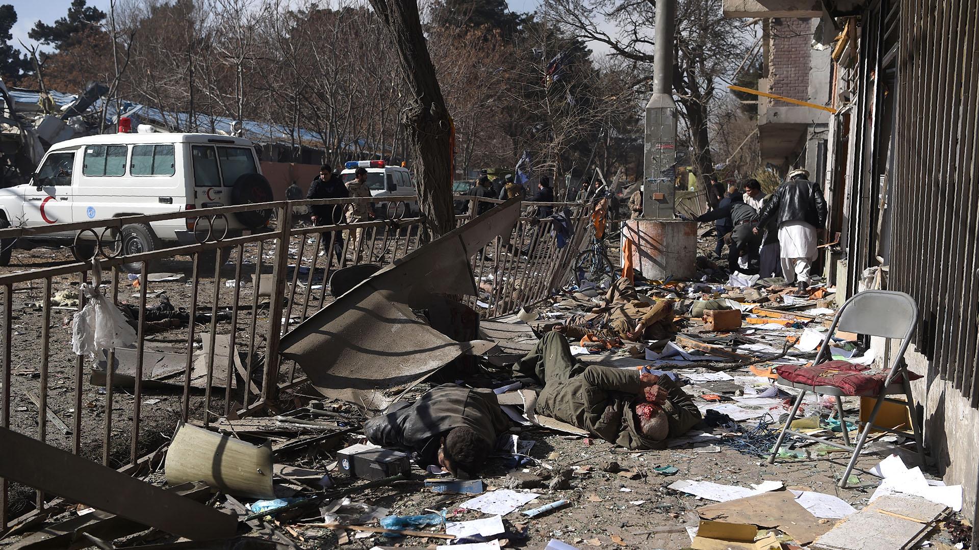 Voluntarios afganos cargan cuerpos tras la explosión frente al antiguo Ministerio del Interior en Kabul (AFP)