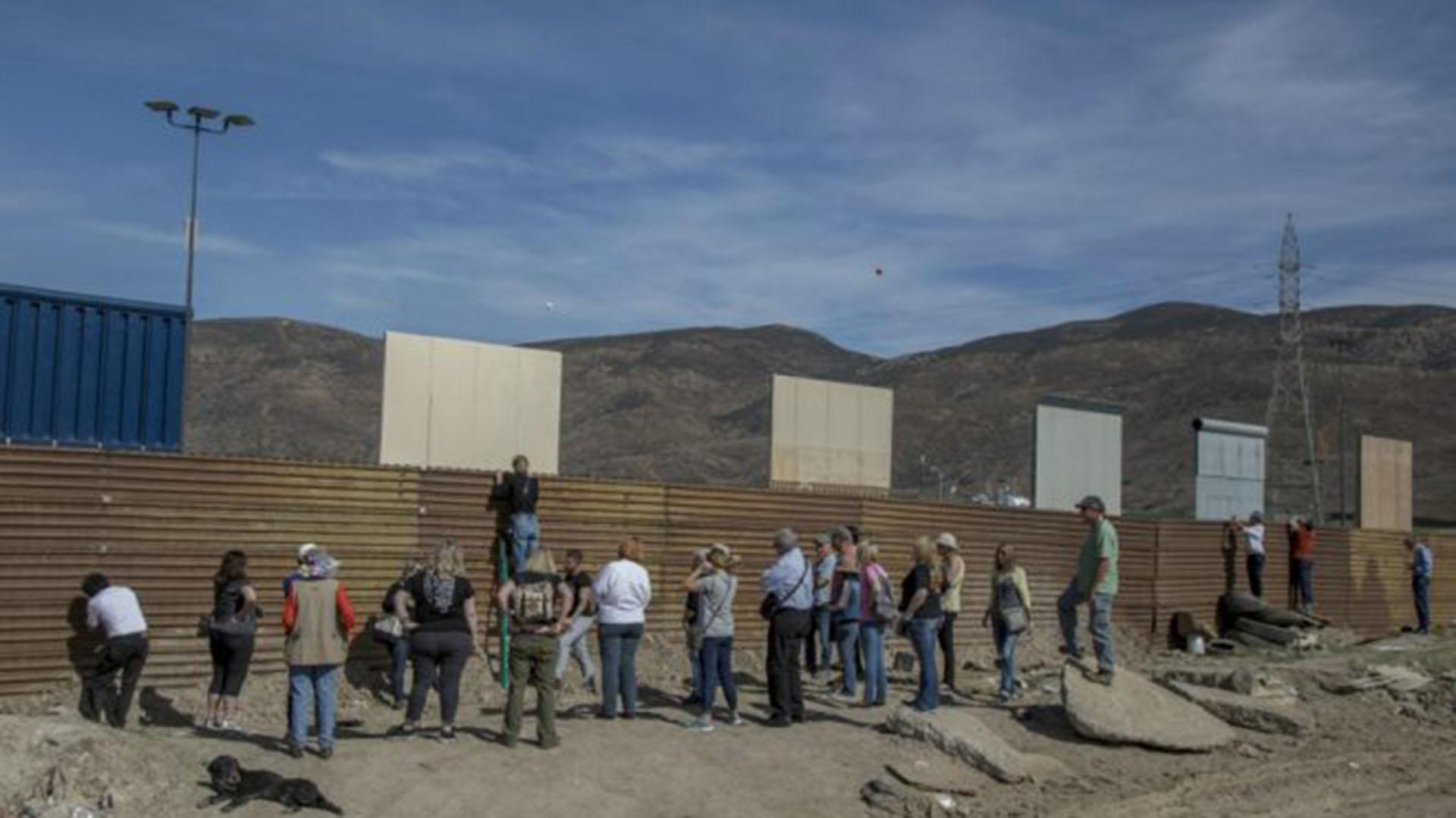 Turistas se congregan en la frontera entre México y Estados Unidos para ver los prototipos del muro. (AP)