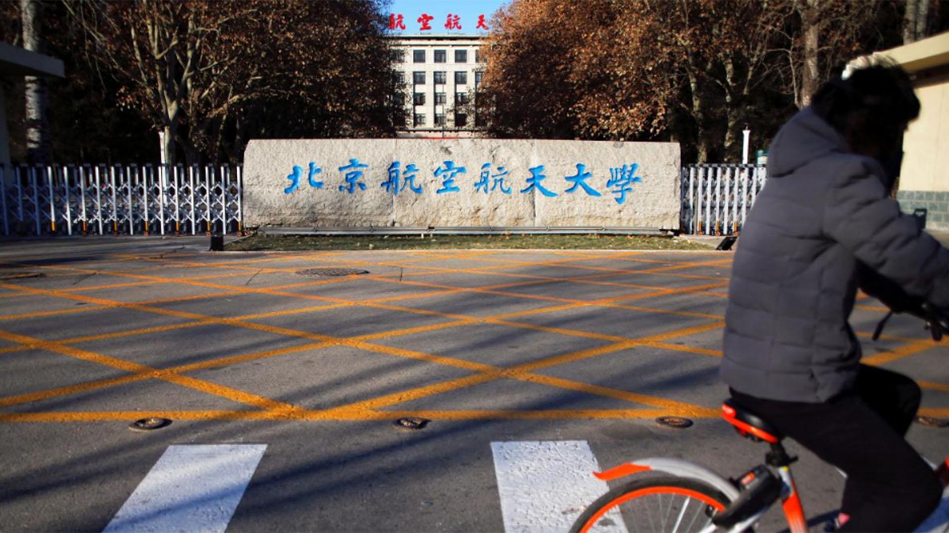 Una persona anda en bicicleta frente a la Universidad de Beihang en Beijing (Reuters)