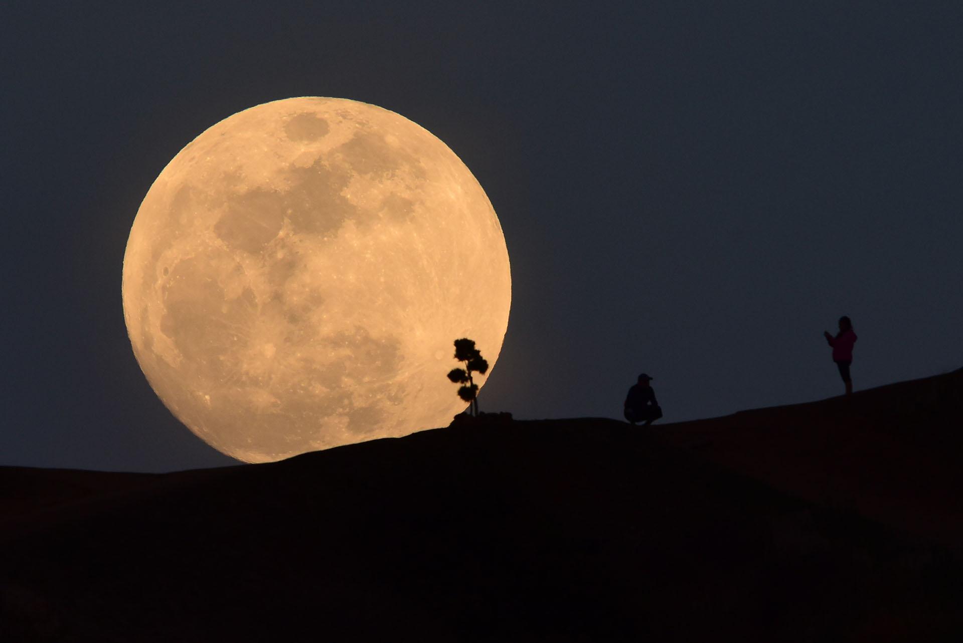 Una persona posa para una foto mientras la luna se levanta sobre Griffith Park en Los Ángeles, California, el 30 de enero de 2018