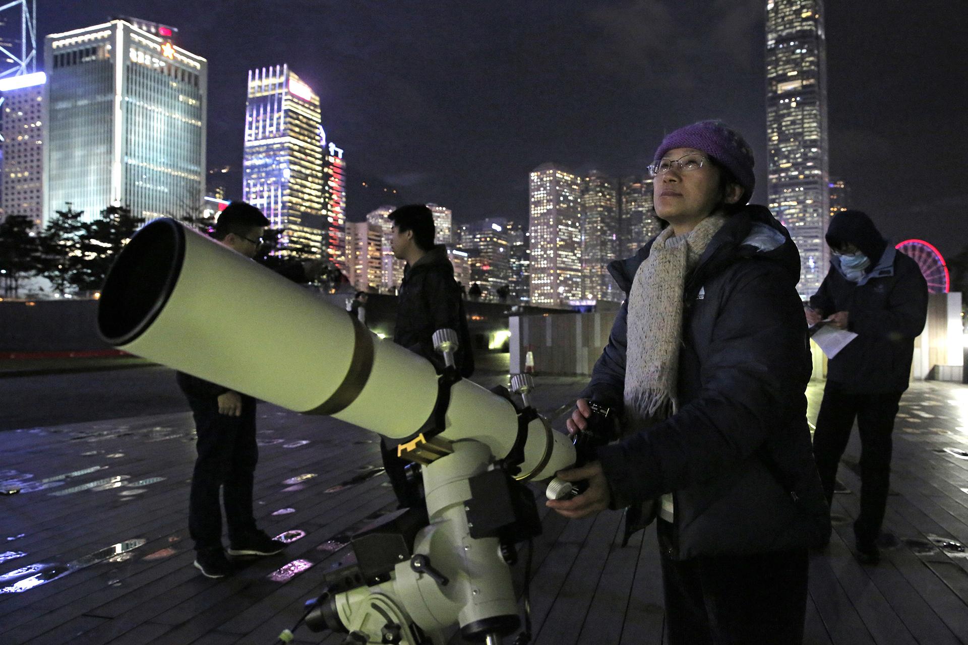 Un astrónomo de Hong Kong utiliza un telescopio para observar la luna a lo largo del Victoria Harbour en Hong Kong, el miércoles 31 de enero de 2018 (AP)