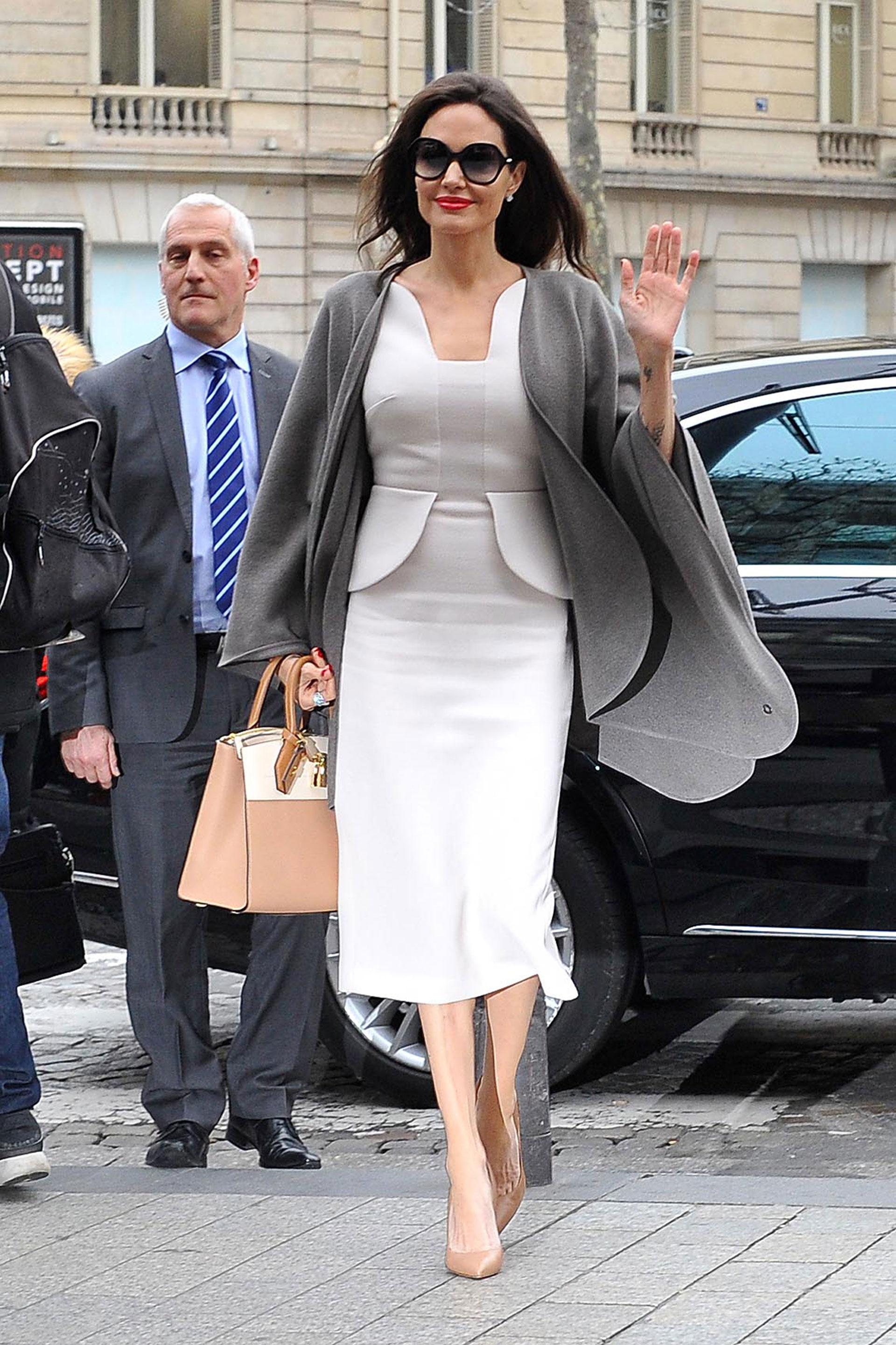 Vestido claro debajo de la rodilla, capa gris, stilettos nude y una gran cartera de mano combinada en su mano derecha: una combinación perfecta