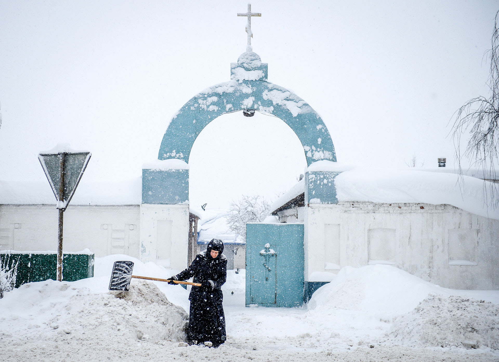 Una monja barre la nieve frente a un convento en la región Vladimirsky