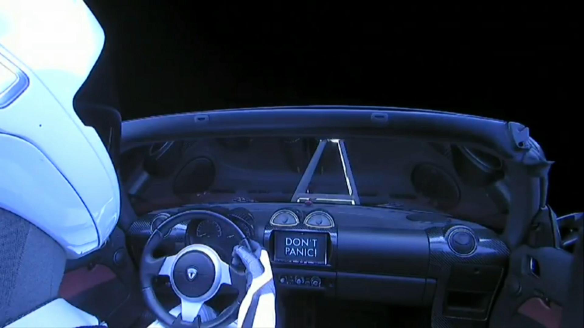 """El Tesla Roadsterfue lanzado al espacio con un muñeco en el asiento del conductor. En esta imagen tomada desdedentro de la nave, se puede observar un cartel que dice """"No entres en pánico"""""""