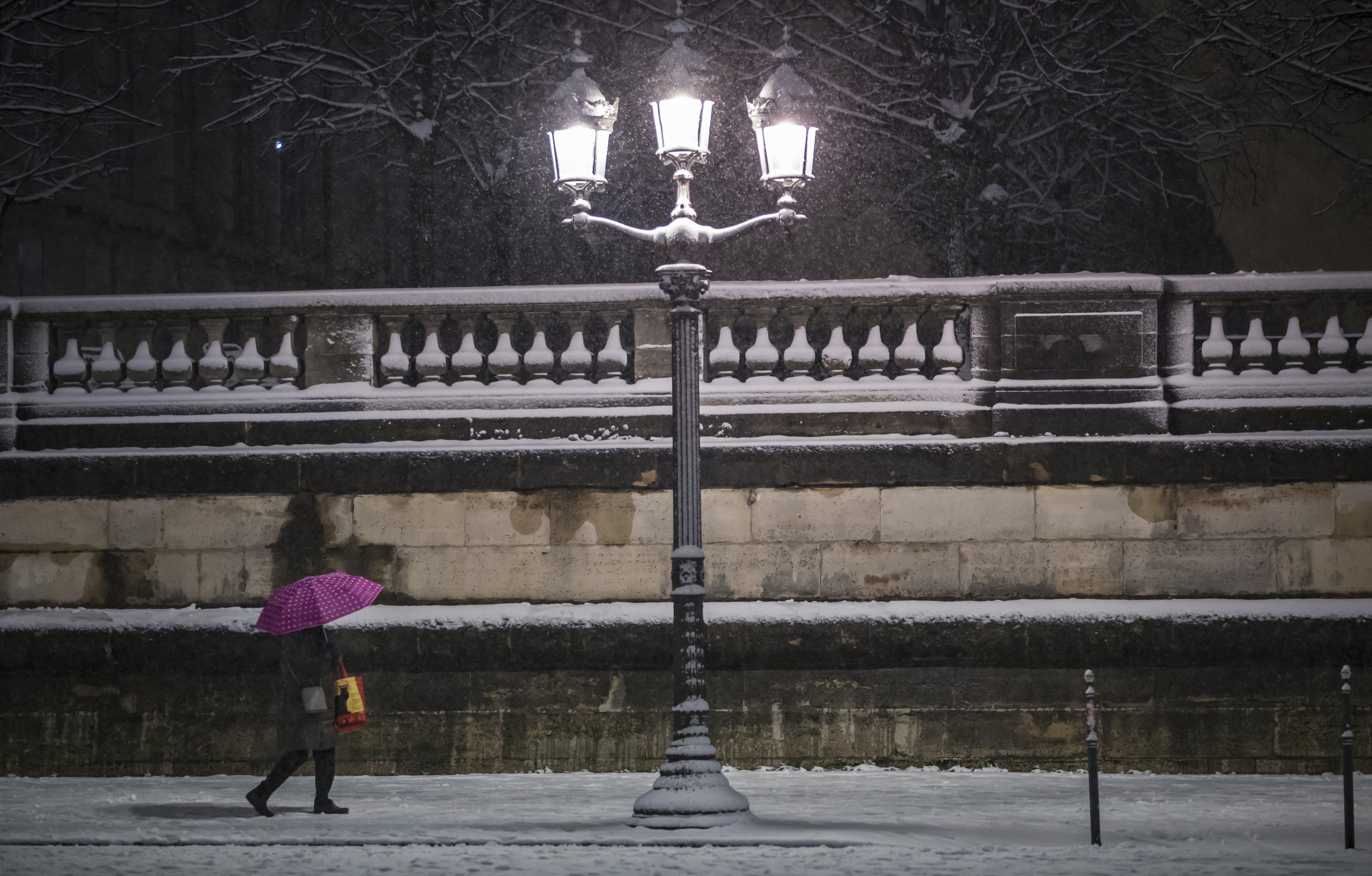 Un peatón camina por la Plaza de la Concordia cubierta por nieve (EFE/Ian Langsdon)