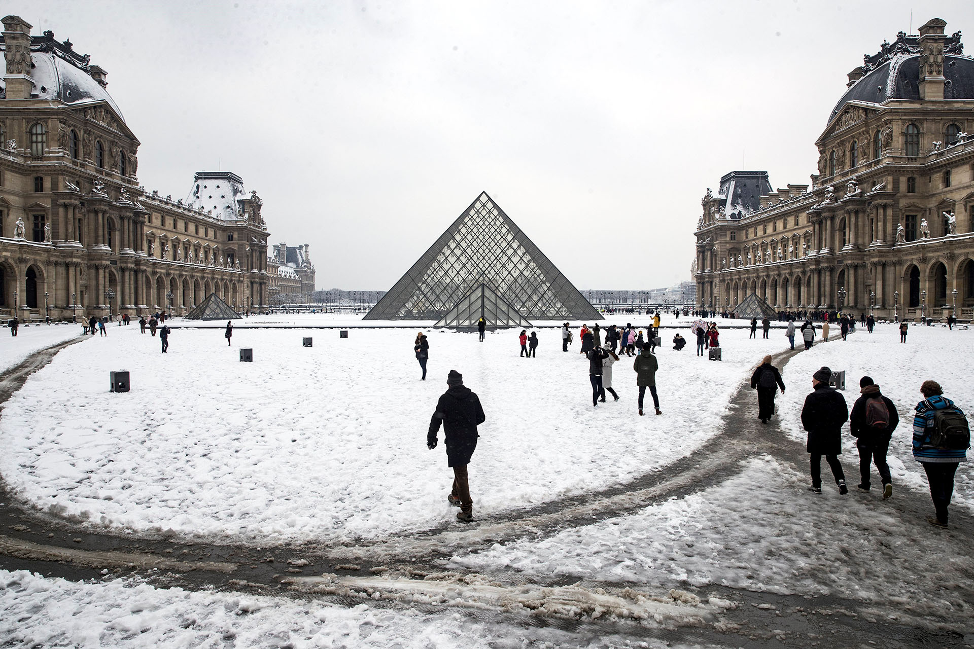 La pirámide del Louvre y los senderos dibujados en medio de la alfombra blanca parisina