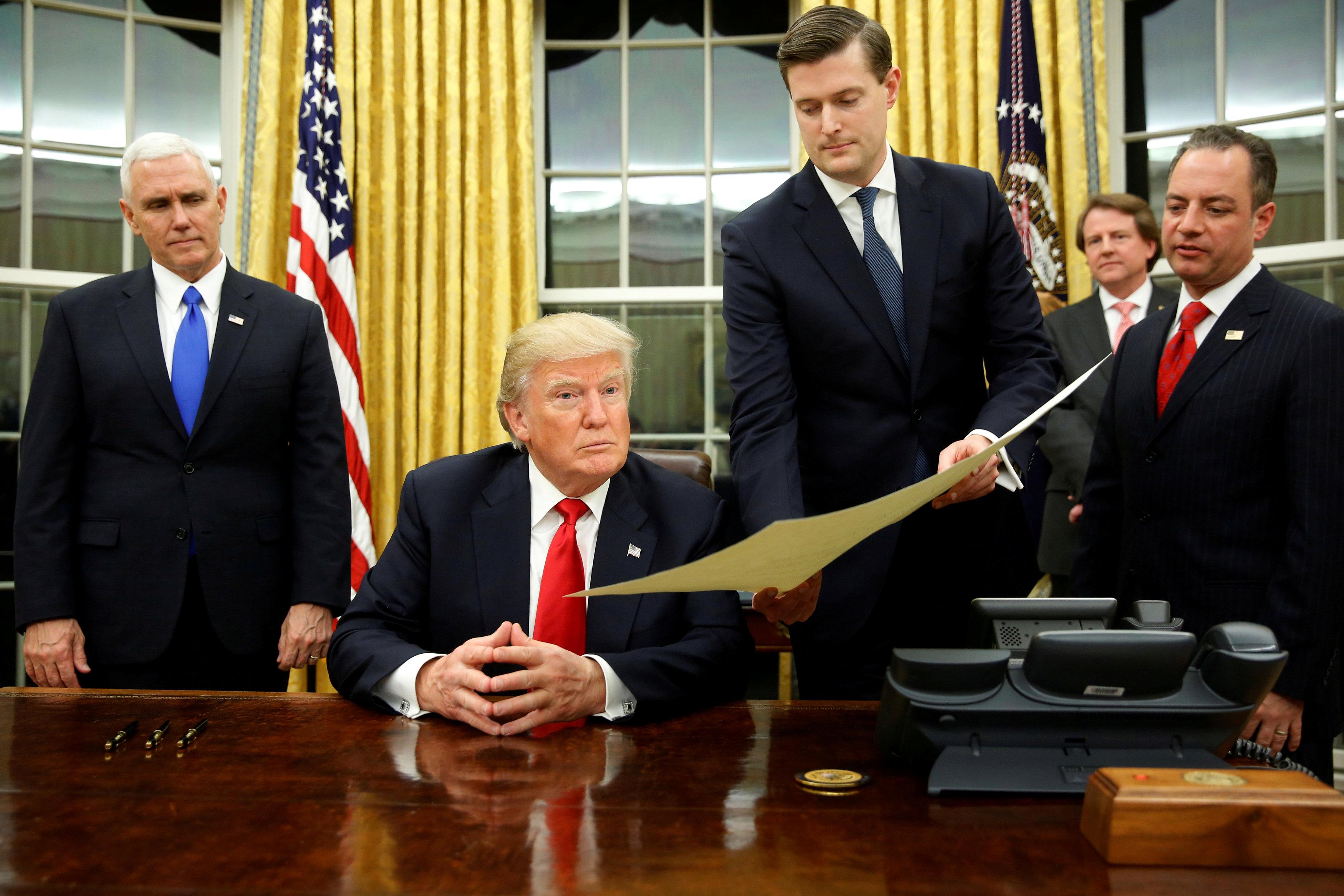 El secretario de personal Rob Porter le entrega un documento al presidente estadounidense Donald Trump (Reuters/Jonathan Ernst/archivo)