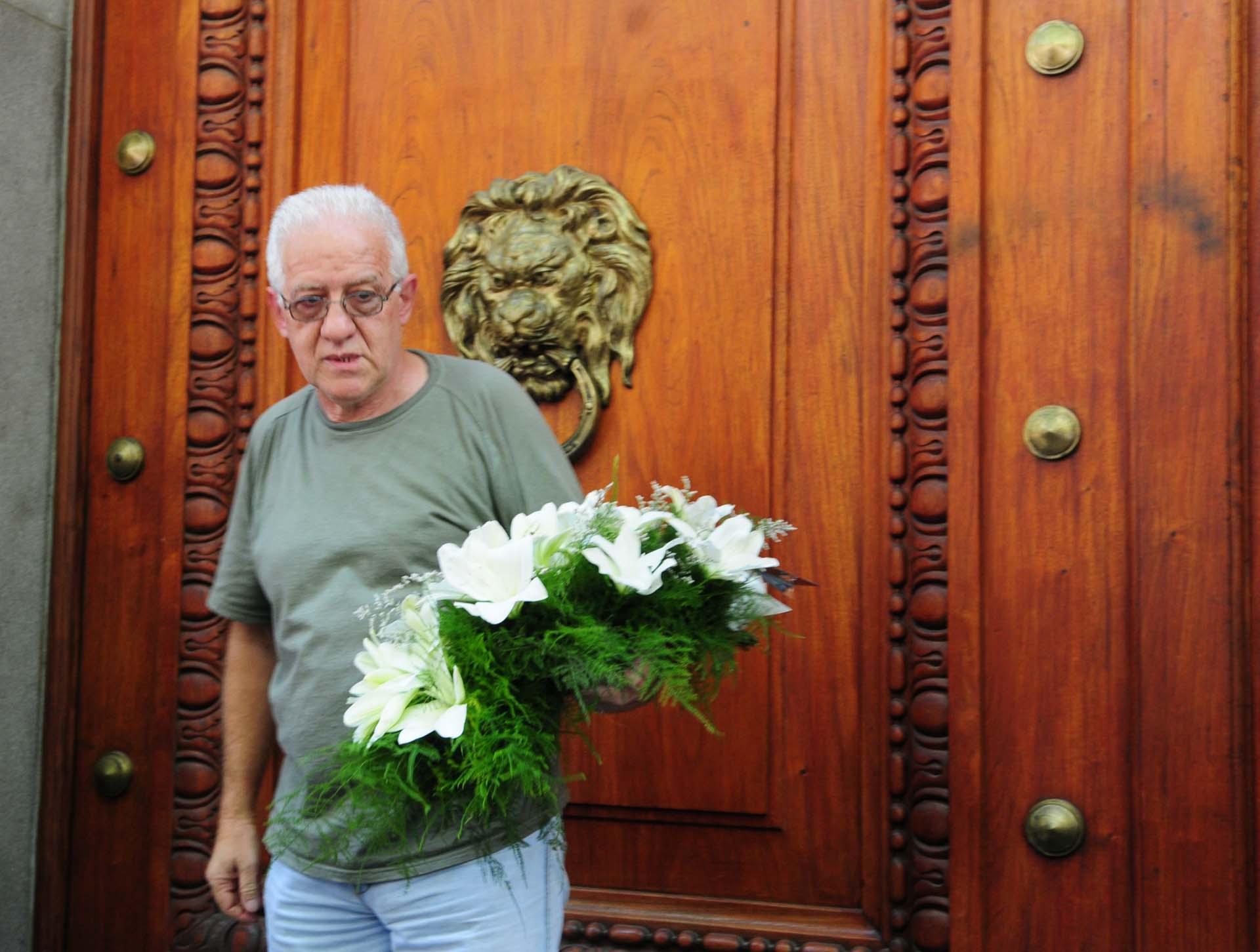 La gente le acercó ramos de flores al cajón