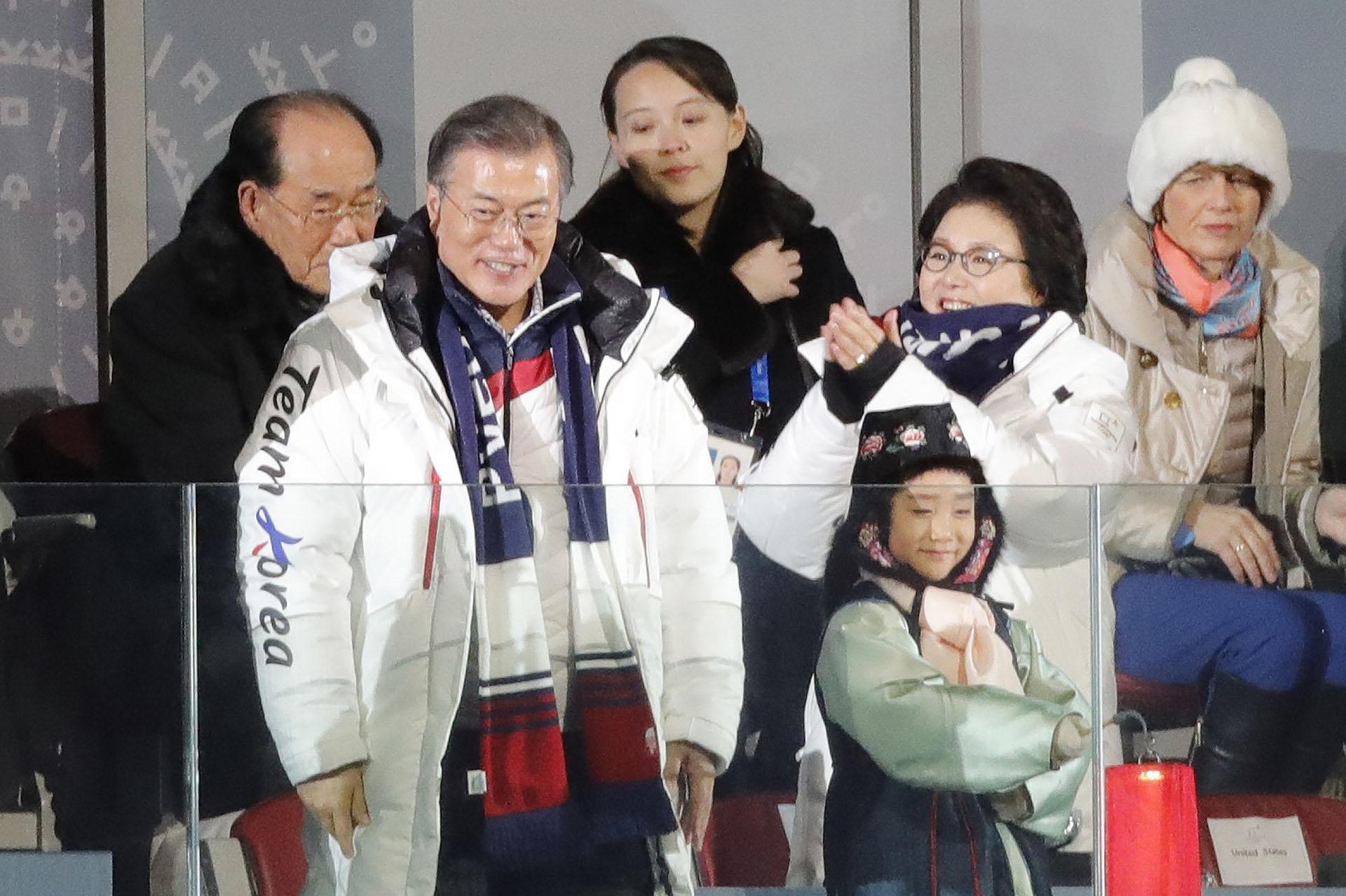 Moon Jae-in sonríe, rodeado de su esposa, Kim Jung-sook (aplaude a su lado) y Kim Yo-Jong, hermana de Kim Jong-un. Detrás suyo, el jefe de la delegación norcoreana, Kim Yong-nam
